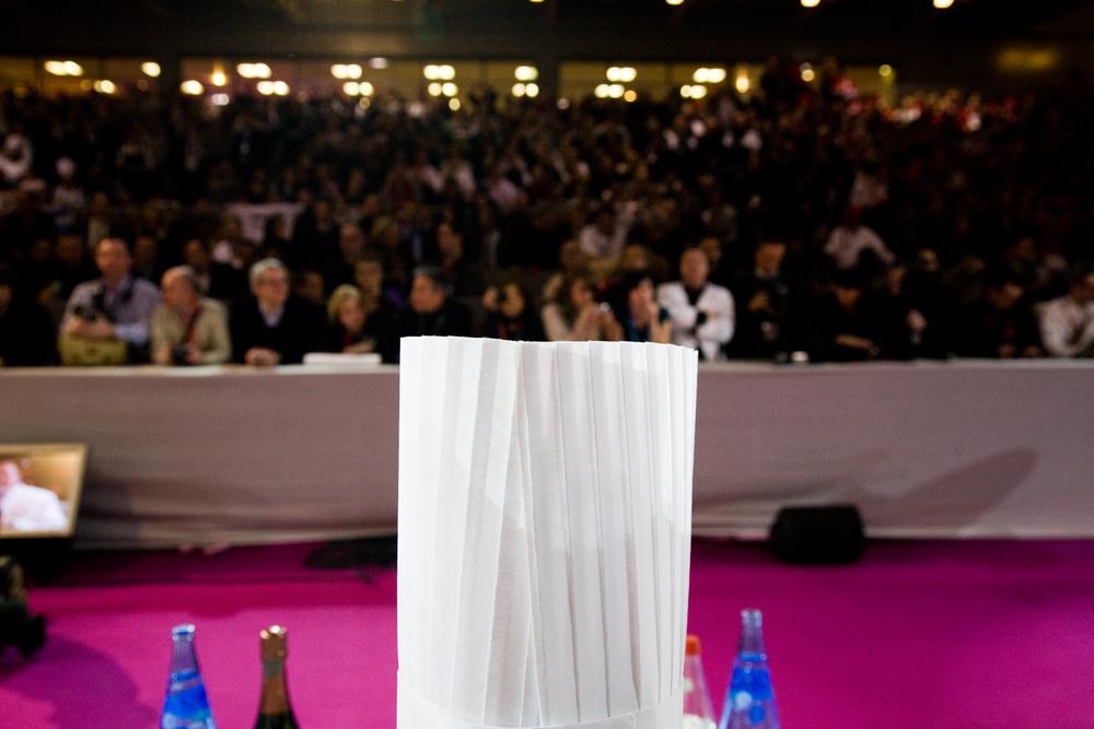 A midi, le jury, composé de 24 chefs internationalement reconnus, prend place à la table. La tribune, comme dans un stade, s'est elle-même remplie. 2000 spectacteurs et supporteurs assisteront aux 2 jours de spectacle.