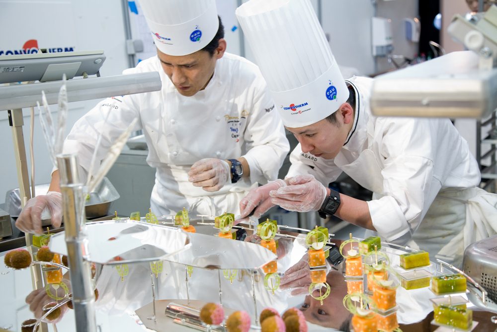 Quelques minutes avant l'envoi du premier plat, l'équipe du Canada effectue la mise en place de son plat. Chaque partie du plat est méticuleusement déposée par le Chef et son second.