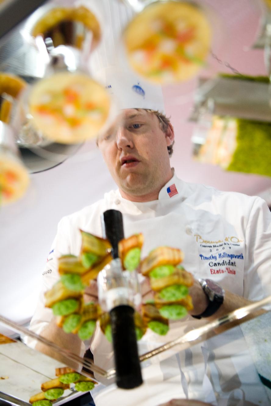 Pendant que le plat de poisson de l'équipe précédente est dégusté par le jury, le chef de l'équipe américaine, Timothy Hollingsworth finit la mise en place de son plat de viande.
