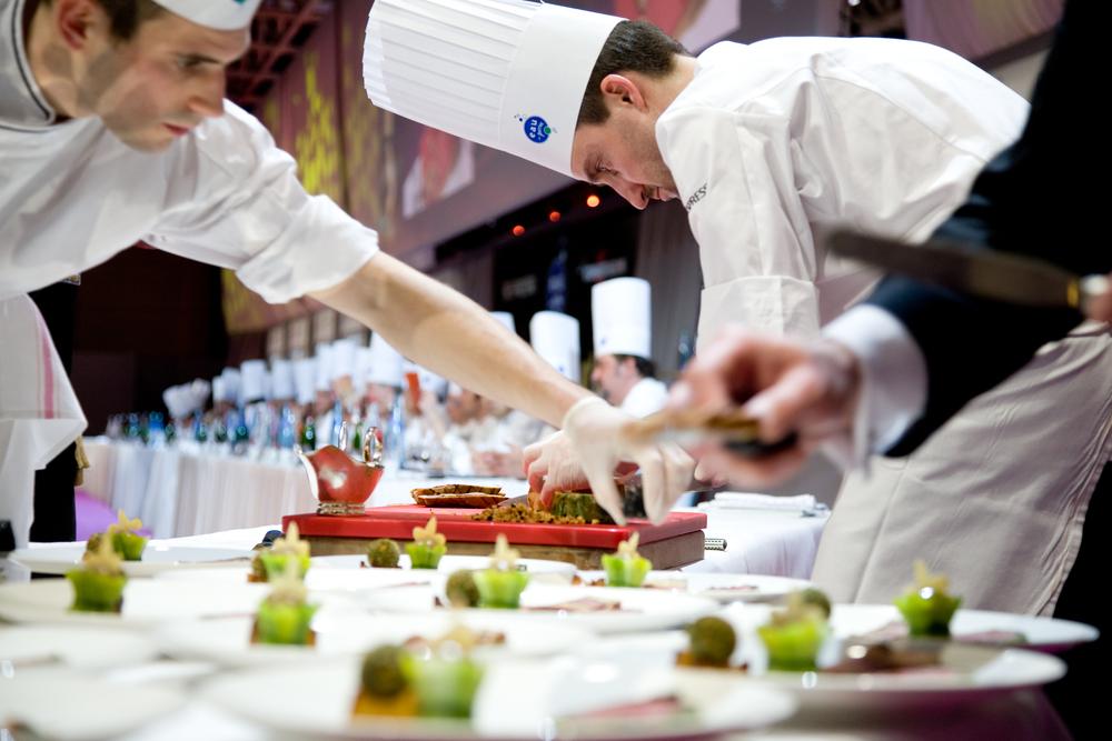 Philippe Mille, le candidat de la France et son second de cuisine découpent et préparent les assiettes pour le jury.