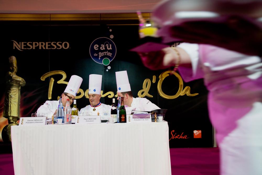 Paul Bocuse, Daniel Boulud et Fabrice Desvignes, Bocuse d'or 2007, jugent l'assiette d'un concurrent pendant que cell d'un autre est présentée au public.