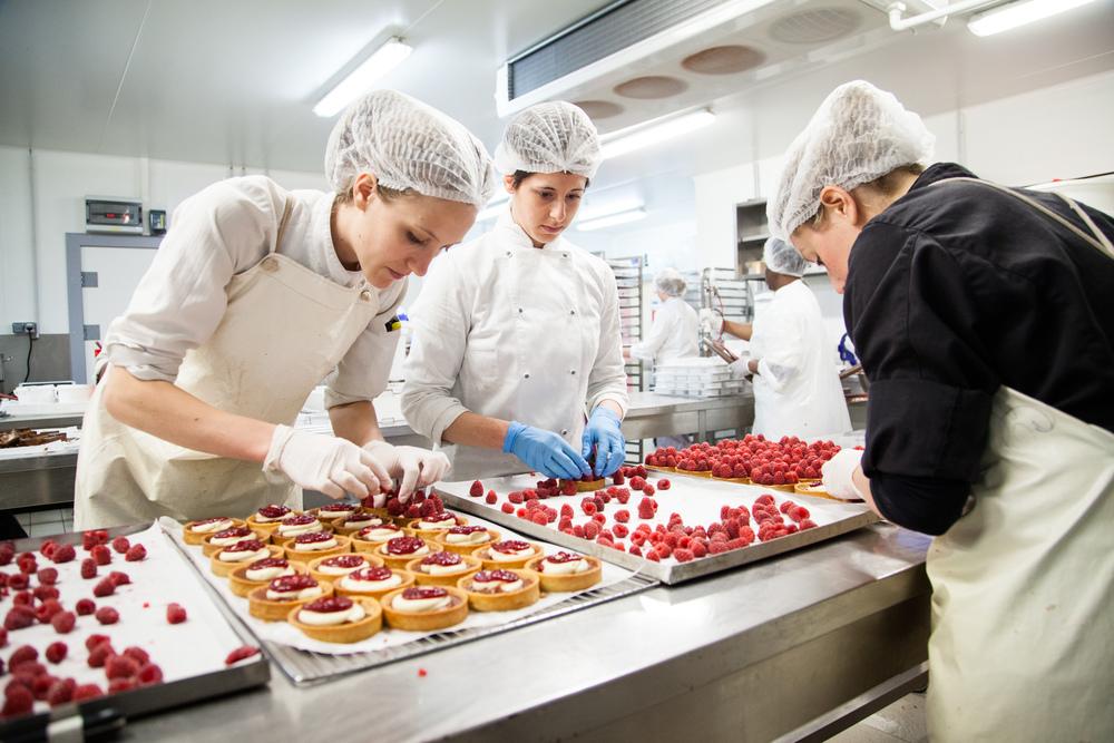 Dans le laboratoire de production, des pâtissières élaborent des tartes à la framboise.