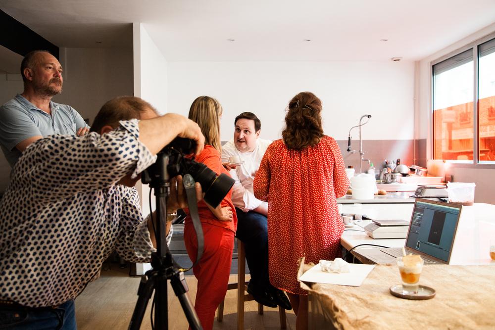 Philippe Conticini en discussion avec la rédactrice en chef d'un magazine santé, pendant que le photographe et le directeur artistique de la revue sont occupés à la prise de vue un dessert.