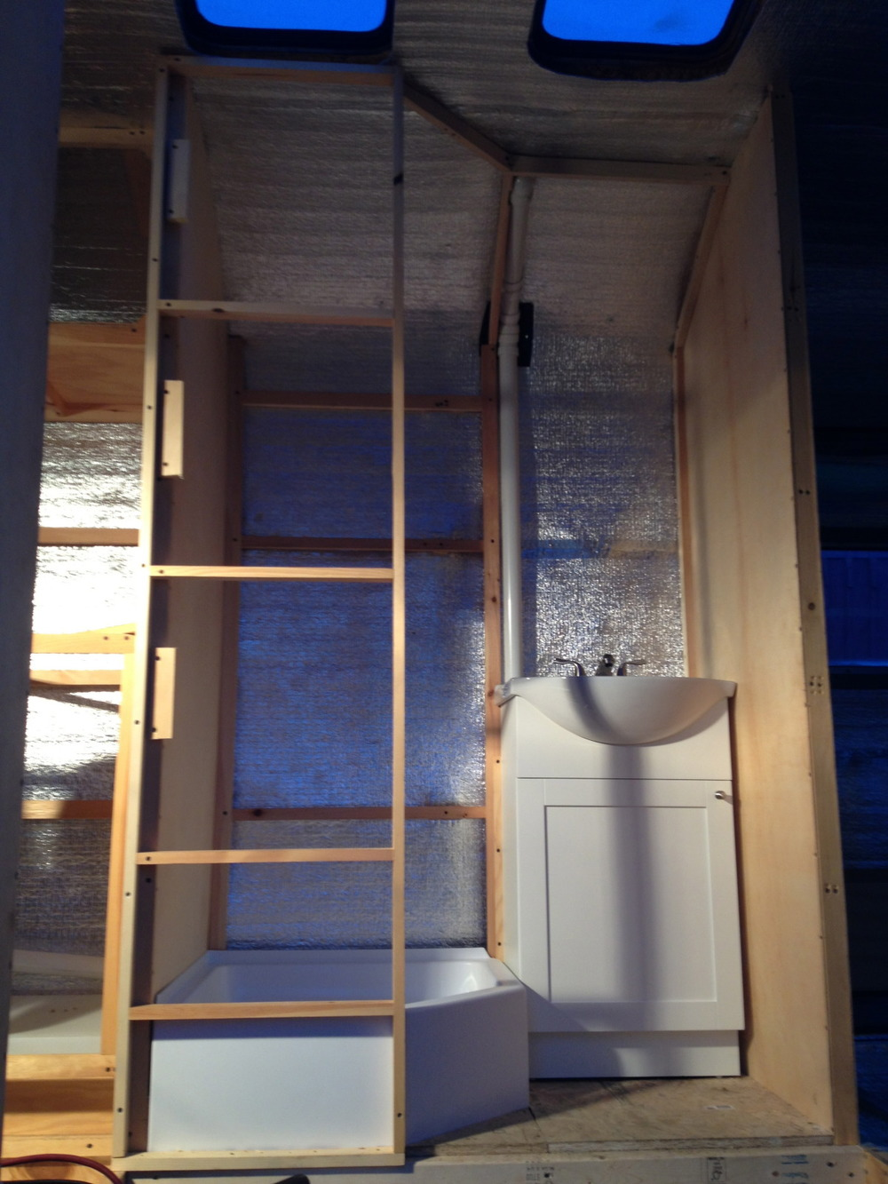 Framing for a section of wall that will double as a hallway wall on one side and a shower stall wall on the other. Bathroom vanity mounted in place over the gray water tank hole and drain pipes.
