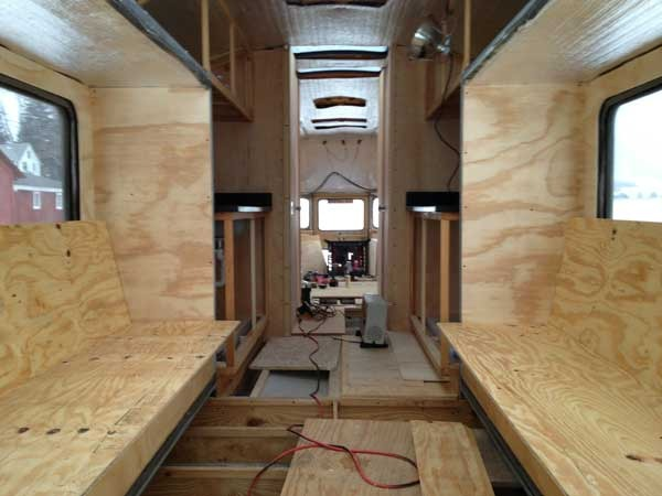 A view from the front of the bus looking back at the finished futon frames in the living room/kitchen area.