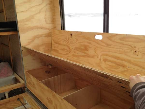 Storage underneath in the sliding drawer with dividers providing support for the futon.