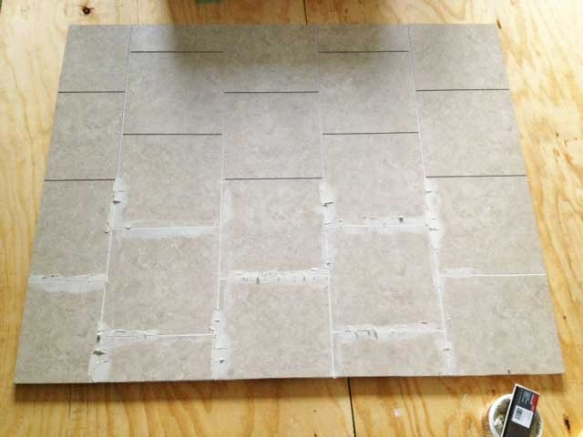 A lot of the new vinyl tile is groutable which helps it do a pretty convincing job of impersonating stone and ceramic tiles.  This was the start of filling grout into all the seams.