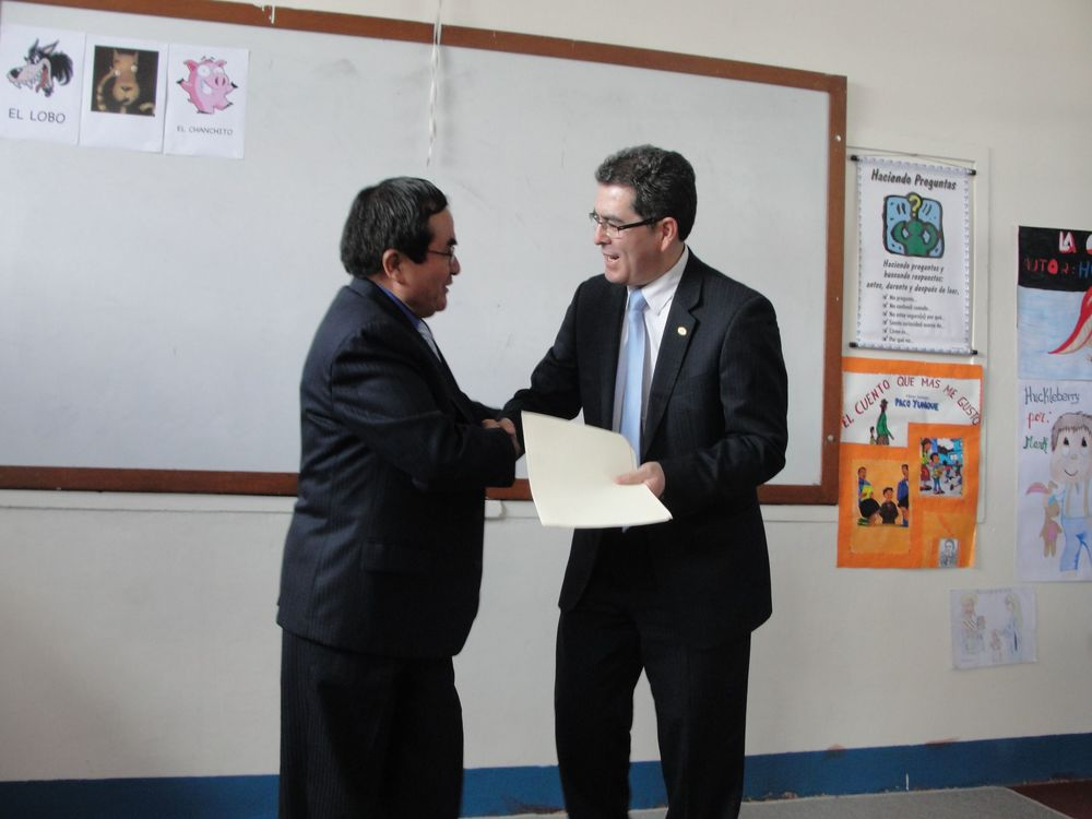 The minister of education handing over the signed papers to Alfredo, CUDA executive director