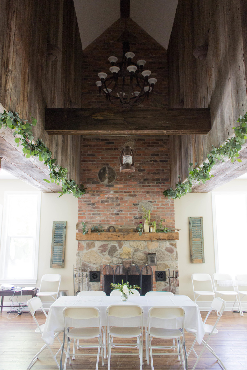 The Great Room, a later addition to the farmhouse, had a fantastic raised section of roof! Garland hung from the old barn wood, with greens and various blooms were placed on the mantle!