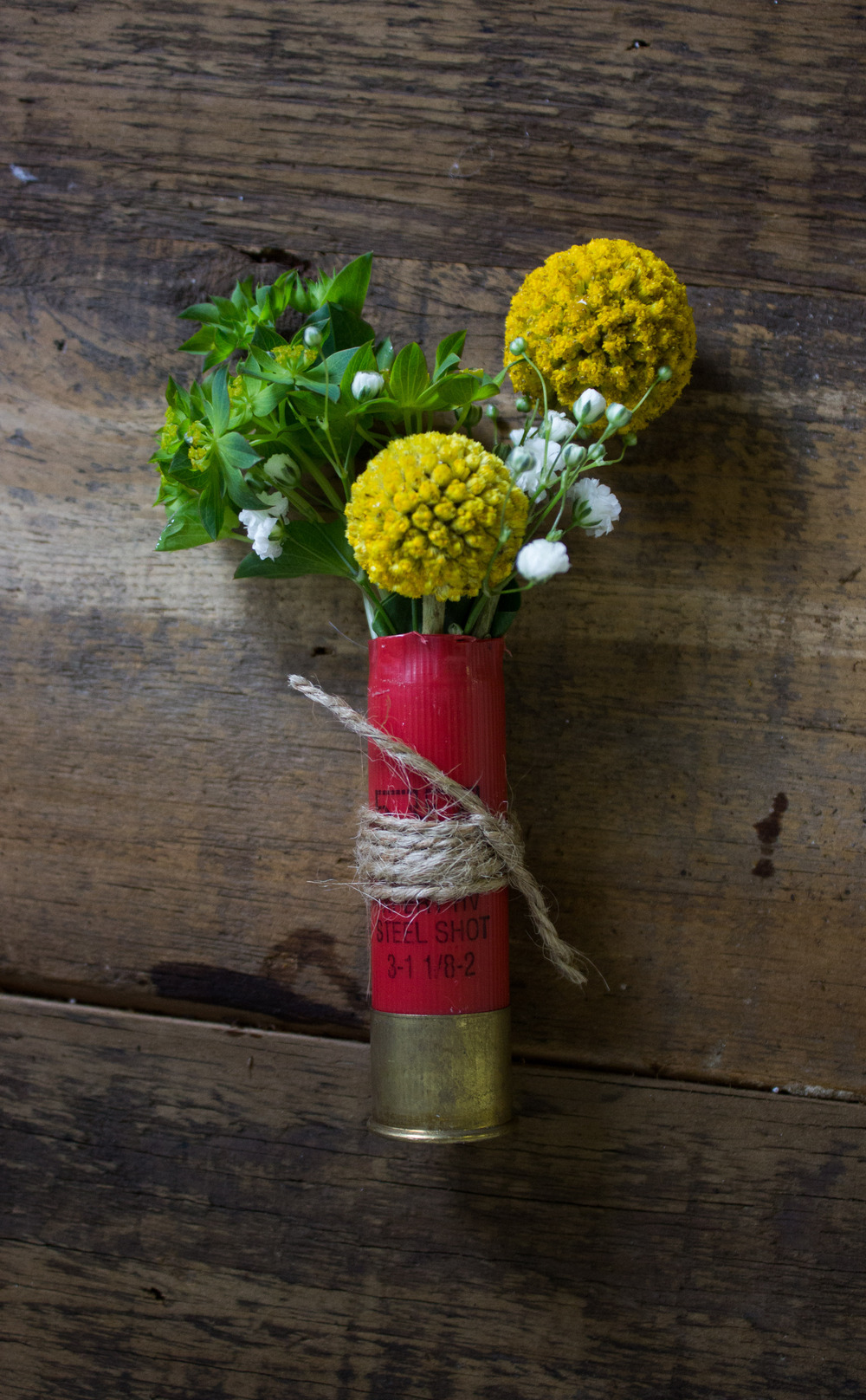 Grooms Boutonniere with Craspedia and Greens in a shotgun casing