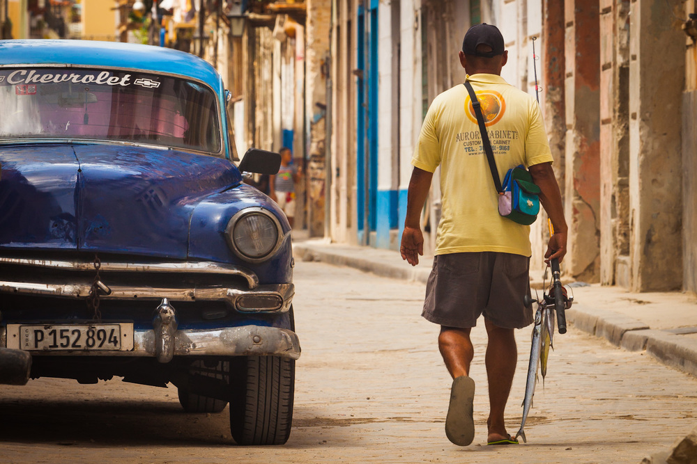 A man walks through old Havana with his dinner. One of my favorite photos from the trip. The jury rigged car next to him is so emblematic of Havana. Notice the chain holding the grill together.200mm f/11 1/160sec