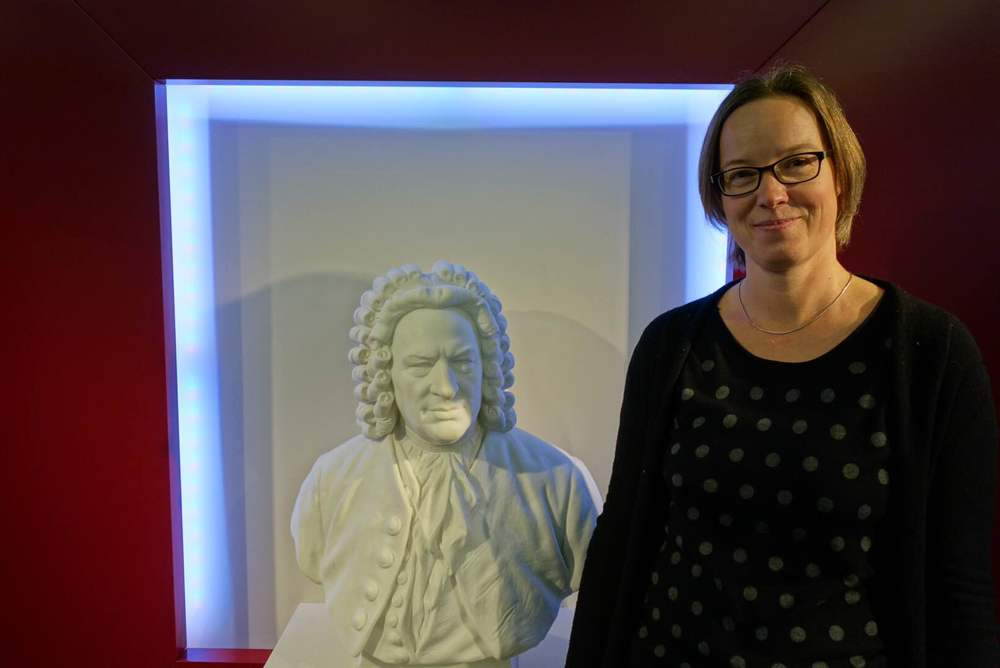Kerstin Wiese, Director of the Bach Museum, standing next to a bust of J.S. Bach. Image: This Week in GErmany