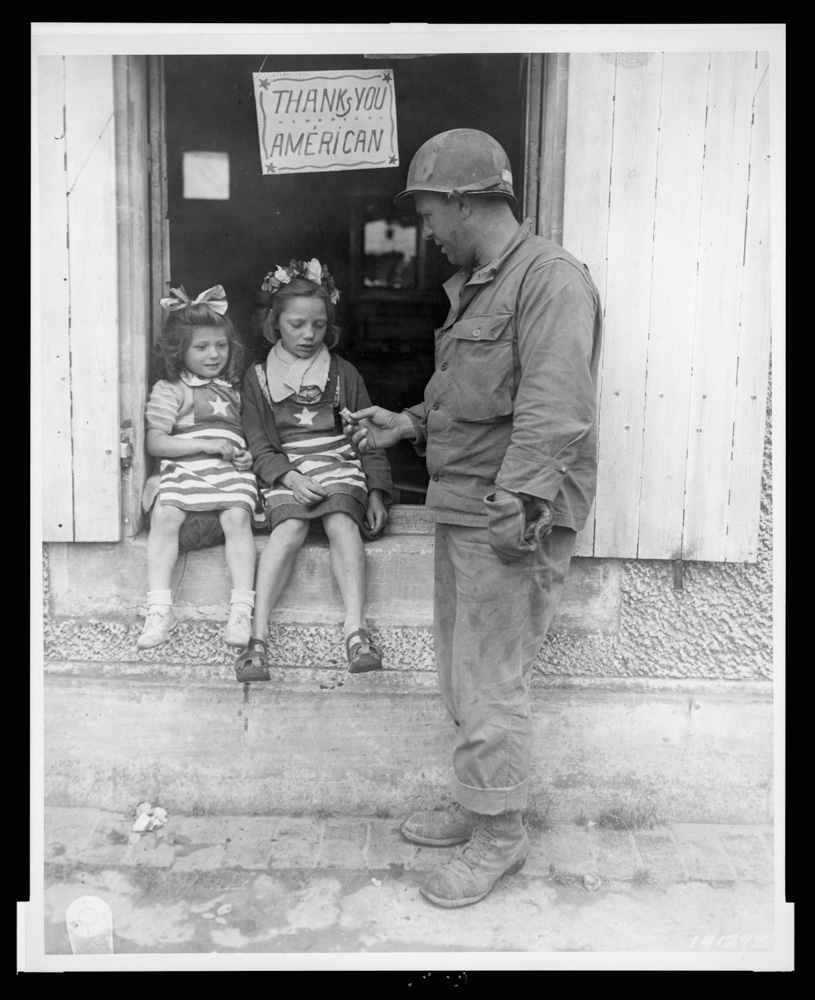 Sgt. Walter P. Goworek treats two little French lasses with some G.I. candy - July 4, 1944