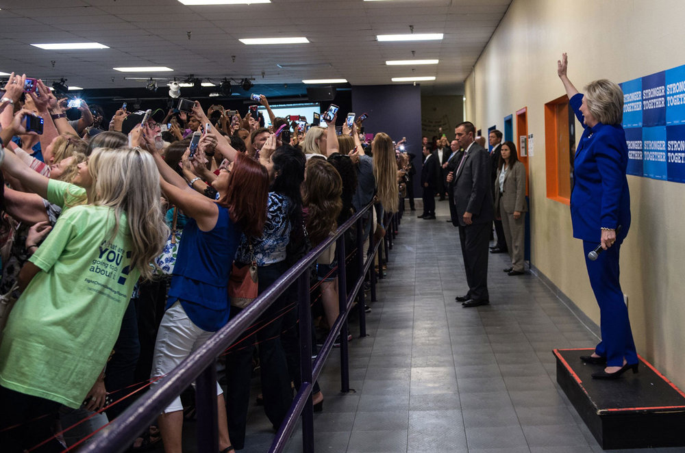Clinton with selfie-ing women. Photo by Barbara Kinney / Hillary for America. Tweeted by Victor Ng