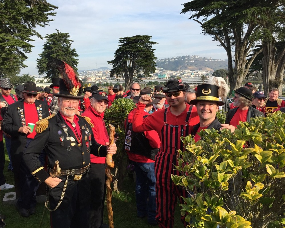 "At Emperor Norton's gravesite during the 2015 Emperor Norton Day celebration of E Clampus Vitus. Emperor Norton is played by Rick Saber. Across from the Emperor, in the white-plumed top hat, is Stephen ""Scooter"" Mitchell, the Noble Grand Humbug (something like the chapter president) of Yerba Buena #1, the E Clampus Vitus ""mother lodge."" At right (with beard) is the Campaign's own Joseph Amster, who has his own ""gig"" playing the Emperor.  Photograph courtesy of Rick Saber."