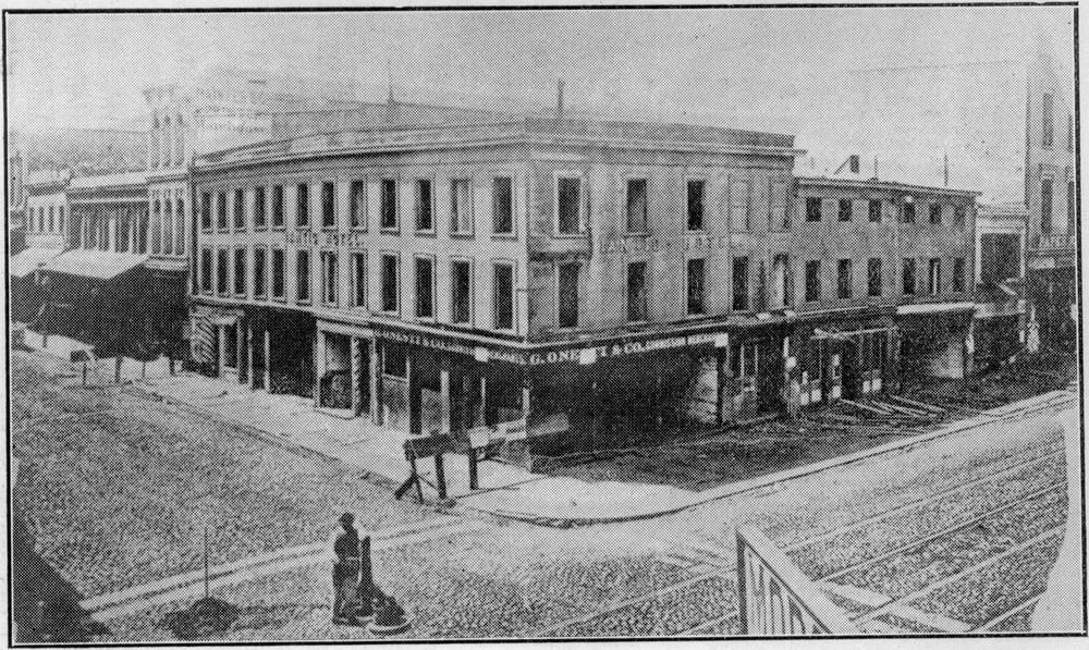 The second Niantic Hotel, at the northwest corner of Sansome and Clay Streets, San Francisco; possibly dated 1865.  Both the printing firm of Cuddy & Hughes and the  Pacific Appeal  newspaper operated out of the building visible at the far right. Photograph from the collection of  James R. Smith .
