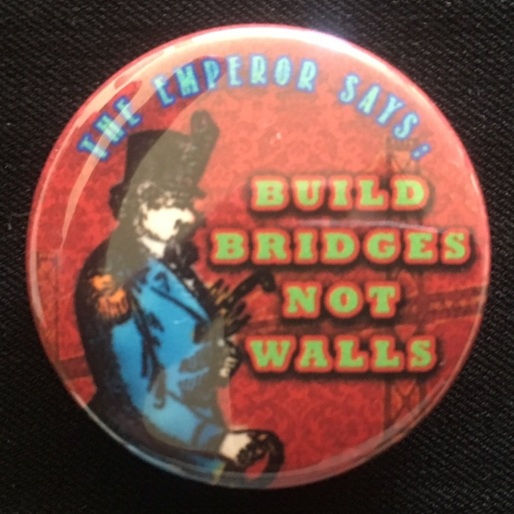 """Build Bridges Not Walls"" pin, February 2017, by Aaron Almanza.  This pin features a colorized detail of an illustration of Emperor Norton, viewable  here , that originally accompanied a front-page profile of the Emperor that appeared in the  San Francisco Chronicle  on 9 November 1879. © 2017 Aaron Almanza. Photo: John Lumea."