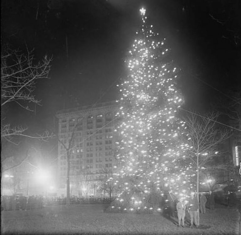 The Christmas tree in Madison Square Park, New York City, on Christmas Eve 1912.  This was one of the first outdoor civic Christmas trees in the United States. The other two — in Boston and in Hartford, Conn. — were lit that same evening. Photograph: Collection of the Library of Congress. Source:  6sqft