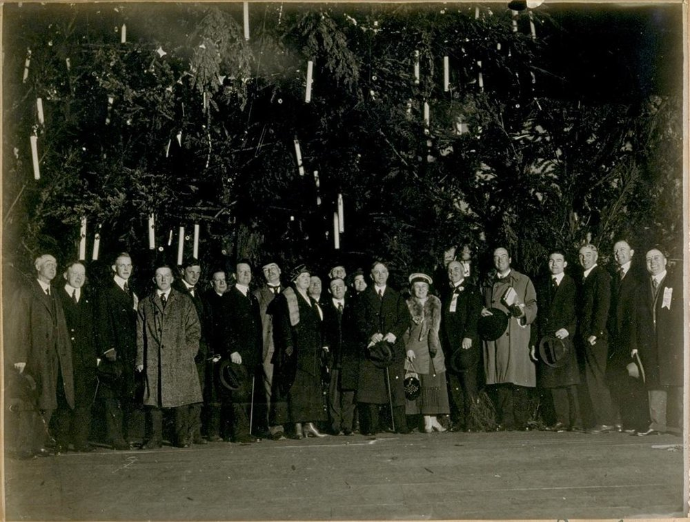 Gathering at the foot of the municipal Christmas tree in Civic Center, San Francisco, 1919.  Sixth from right is San Francisco Mayor James Rolph. Photograph in the Jesse Brown Cook Scrapbooks Documenting San Francisco History, c.1895–1936, Bancroft Library, UC Berkeley. Source:  Calisphere .