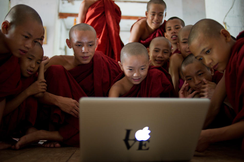 In 2009, Jean befriended Thuriya, a young novice monk from Mandalay (centre) and travels back to Myanmar once every few years to visit him. Here he looks at photos of him and his friends from an excursion.