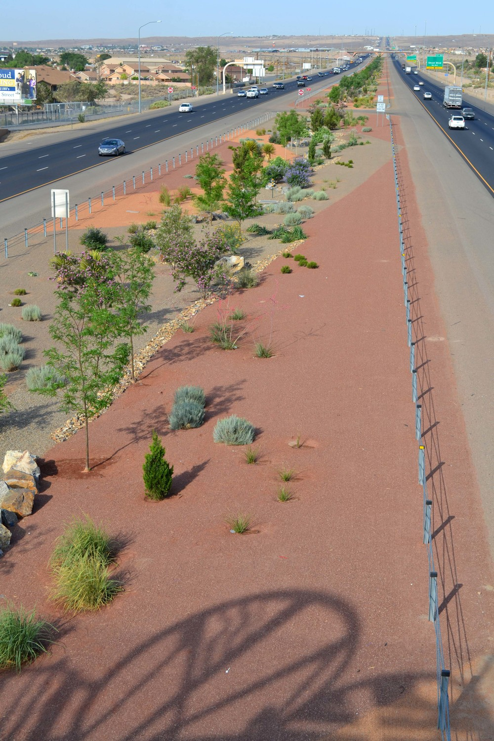 Art on the bridge above the highway casts an ornamental shadow