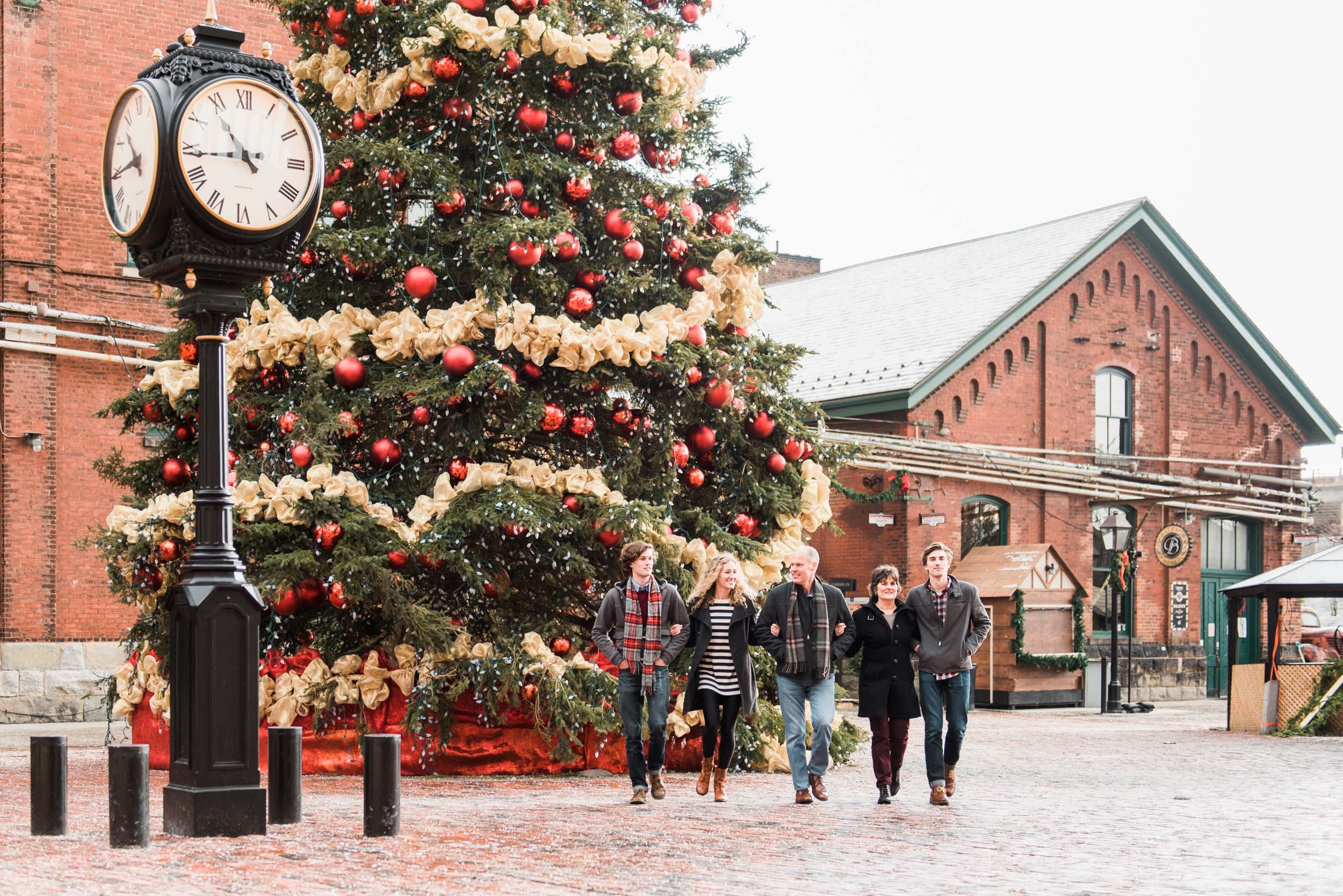Family walking together with arms wrapped around each other beside a large outdoor Christmas tree in Toronto, Canada on a family trip