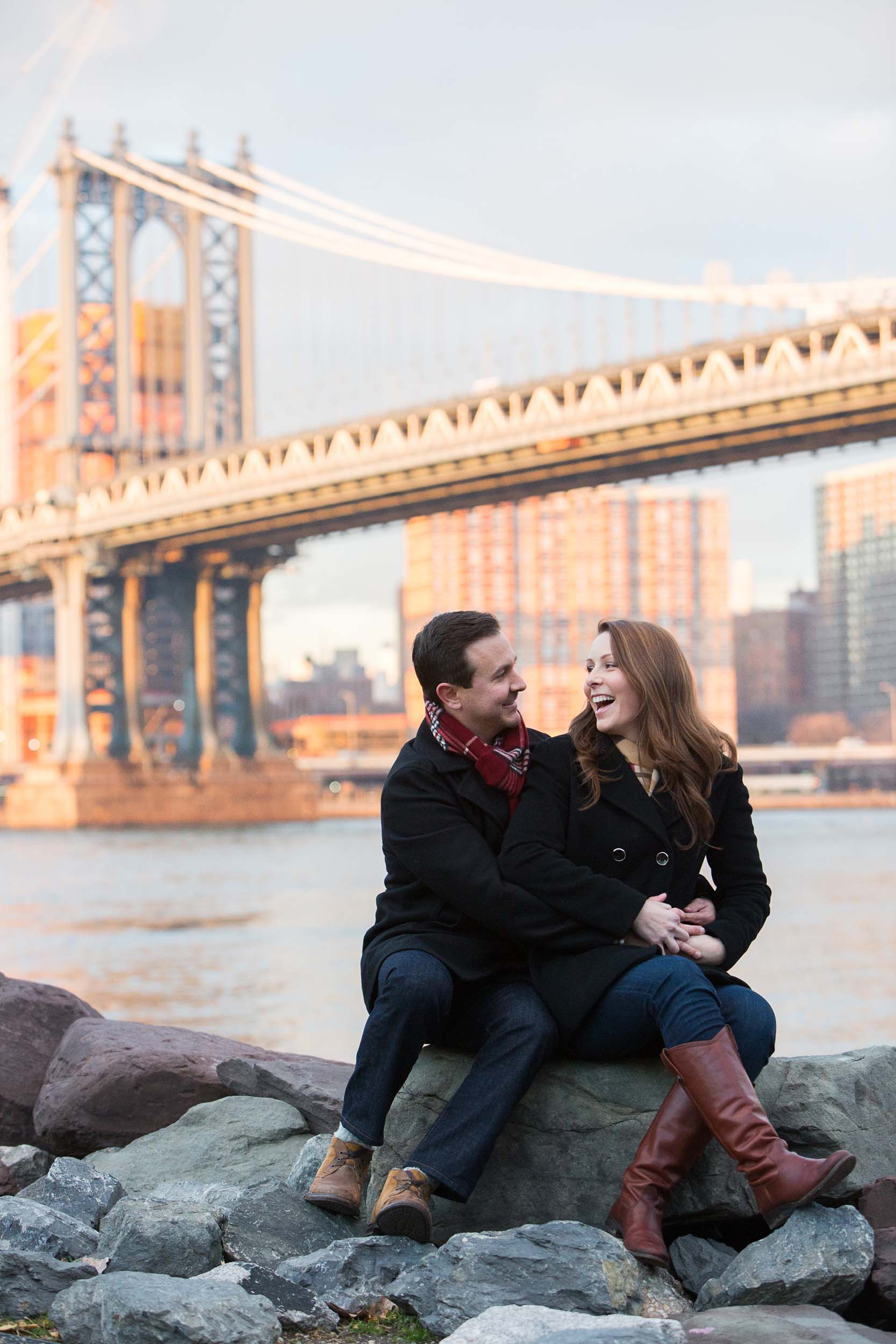 Couple sitting on rocks together laughing with the Brooklyn Bridge in the background in New York City, USA