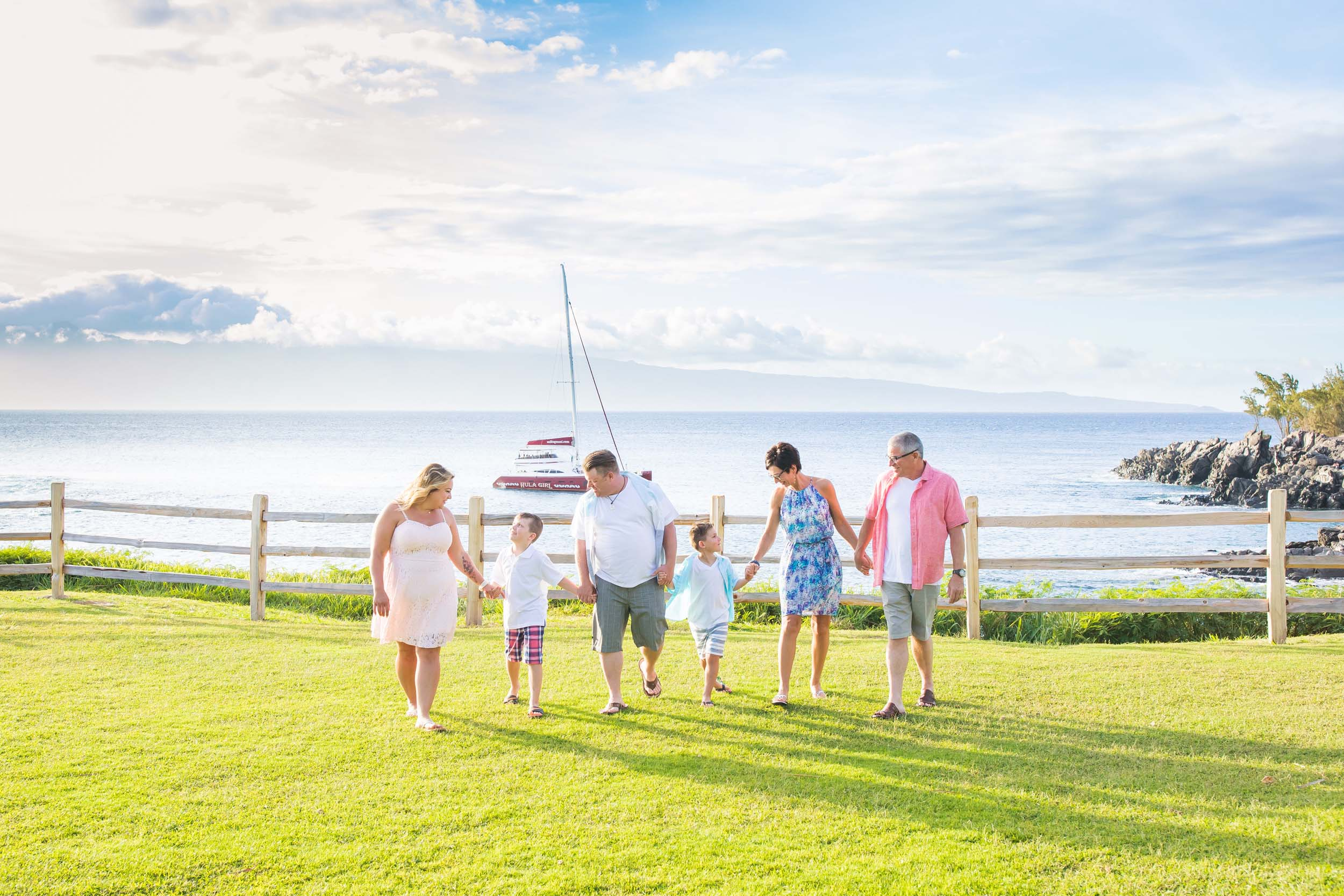 Multi-generational family holding hands and walking along the grass together in Maui, USA
