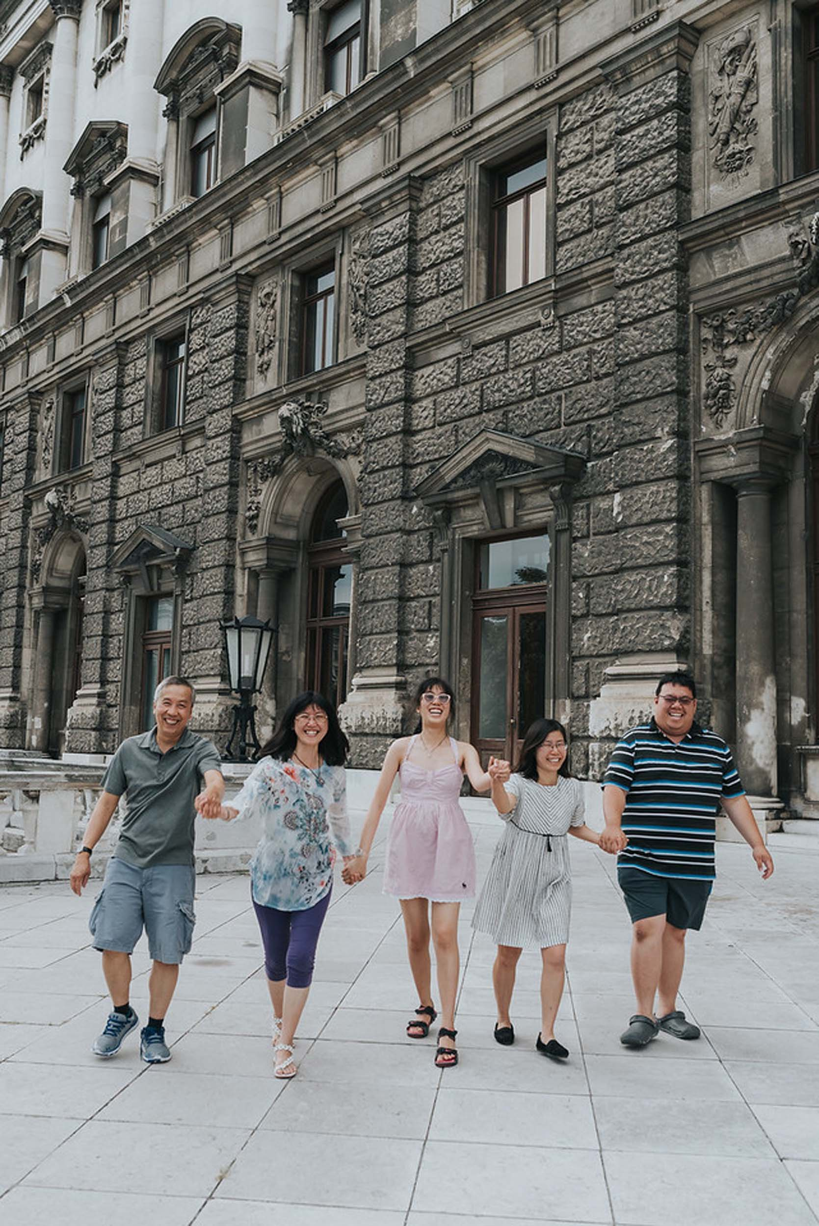 Family holding hands and walking together on a family trip in Vienna, Austria