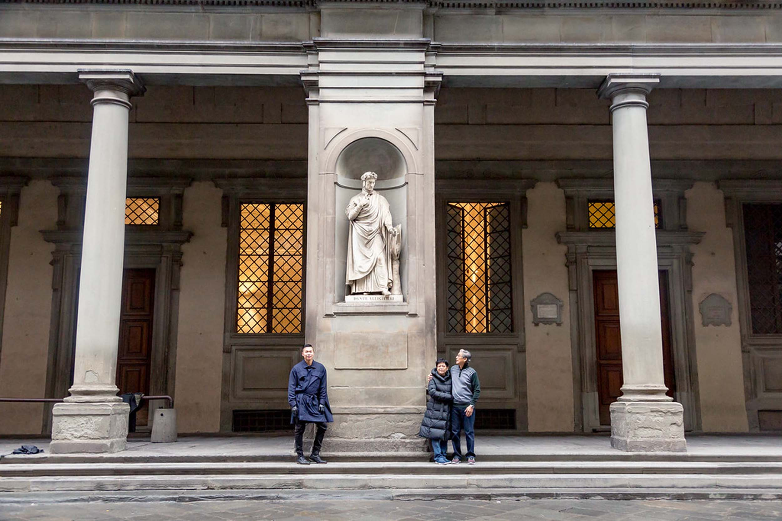 Asian father, mother and adult son standing in front of the statue of poet Dante Alighieri on a family trip together in Florence, Italy