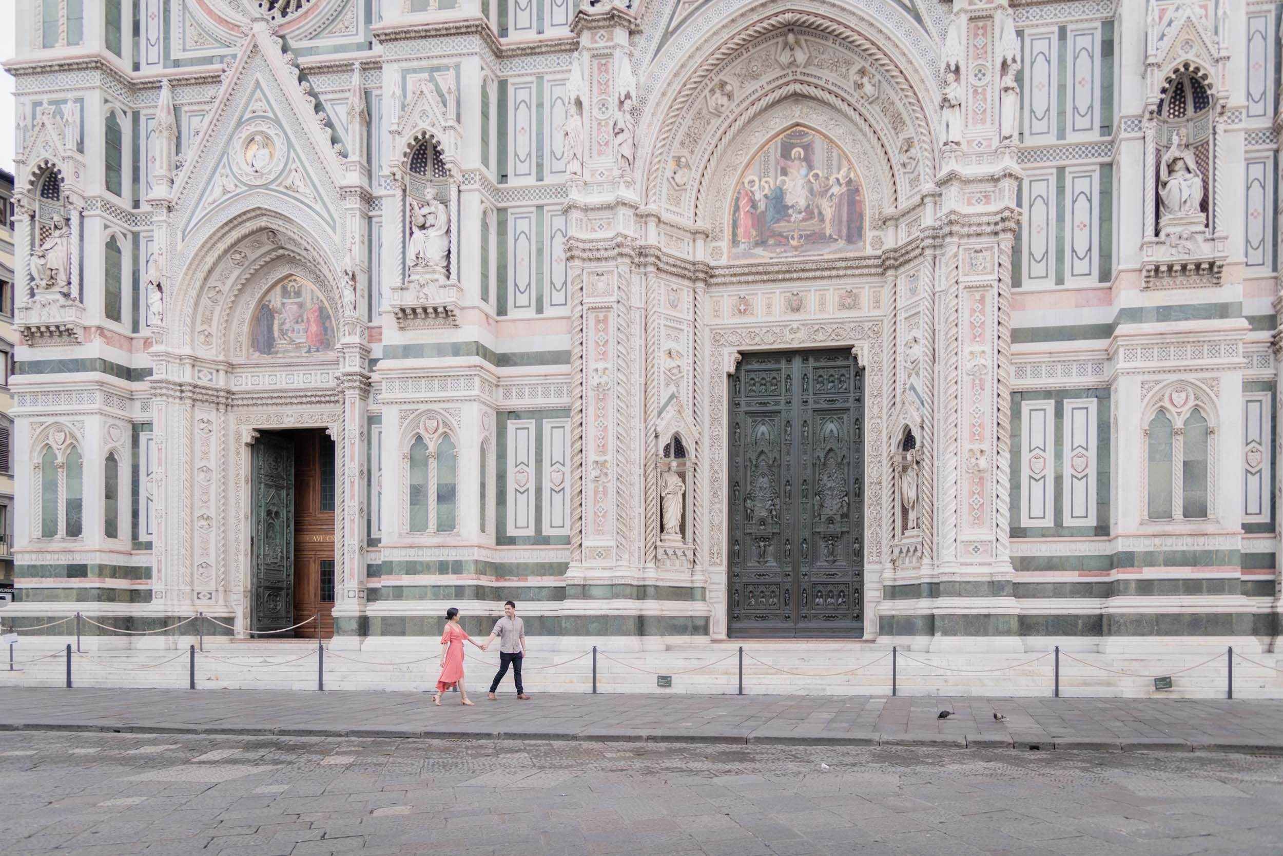 Asian couple holding hands and walking in front of The Duomo on a couples trip in Florence, Italy