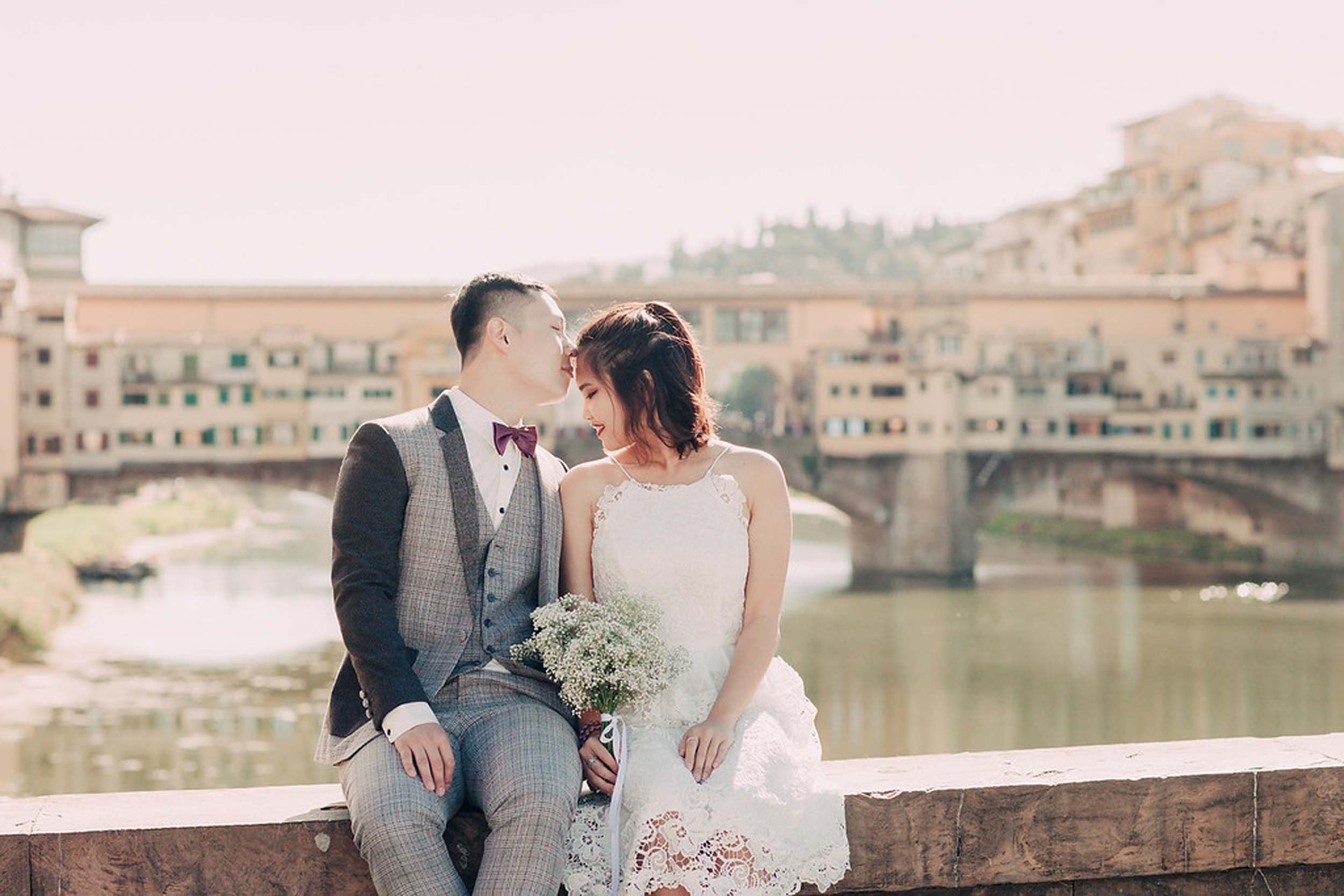 Man kissing partner's forehead sitting on bridge ledge together at Ponte Vecchio in Florence, Italy