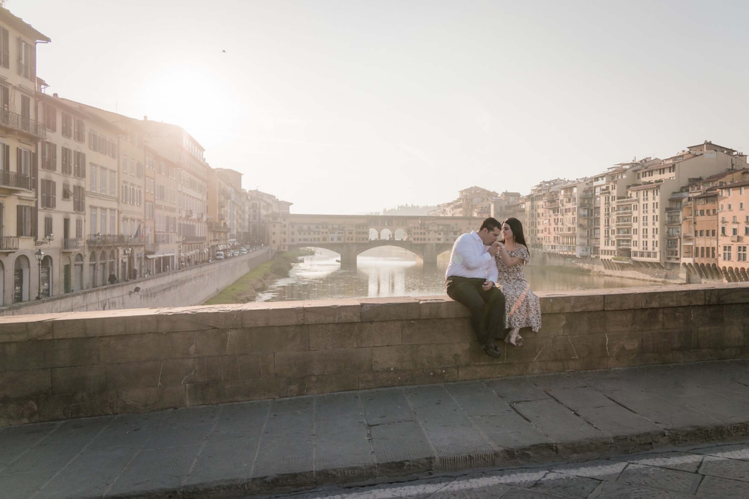 Man kissing partner's hand sitting on bridge ledge together at Ponte Vecchio in Florence, Italy