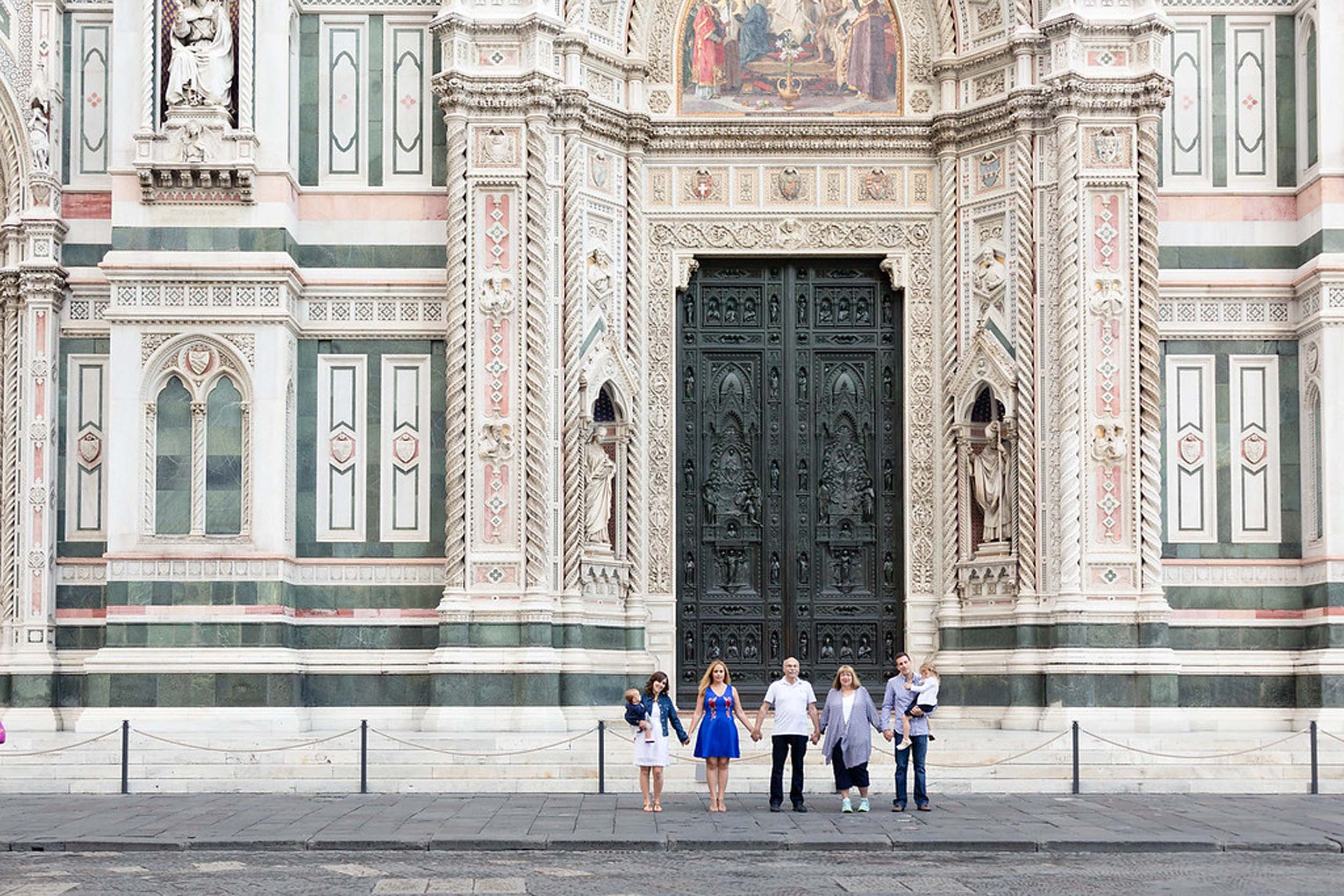 Multi-generational family of seven standing in front of The Duomo on a family trip in Florence, Italy