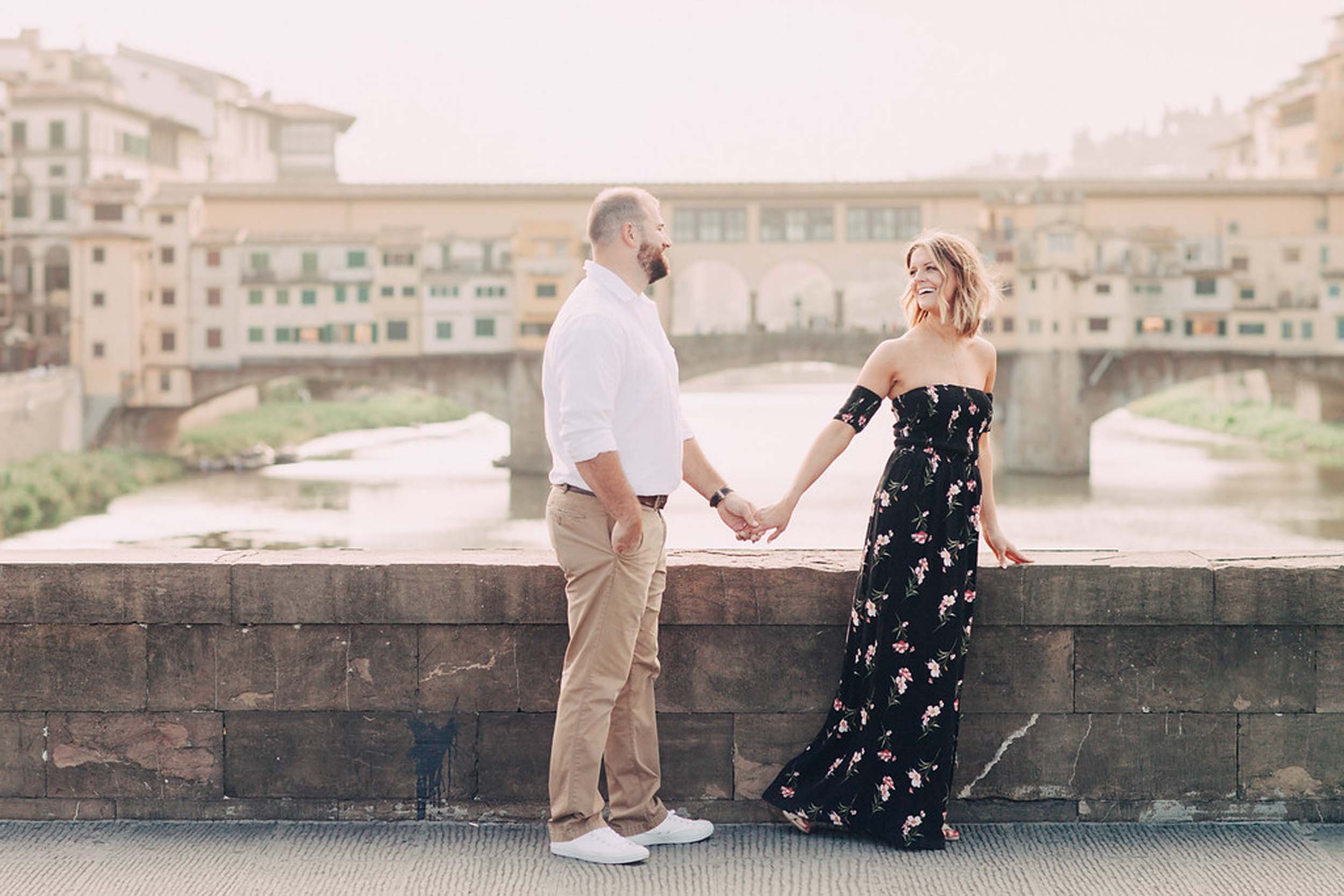 Couple standing on bridge holding hands in front of Ponte Vecchio on couples trip in Florence, Italy