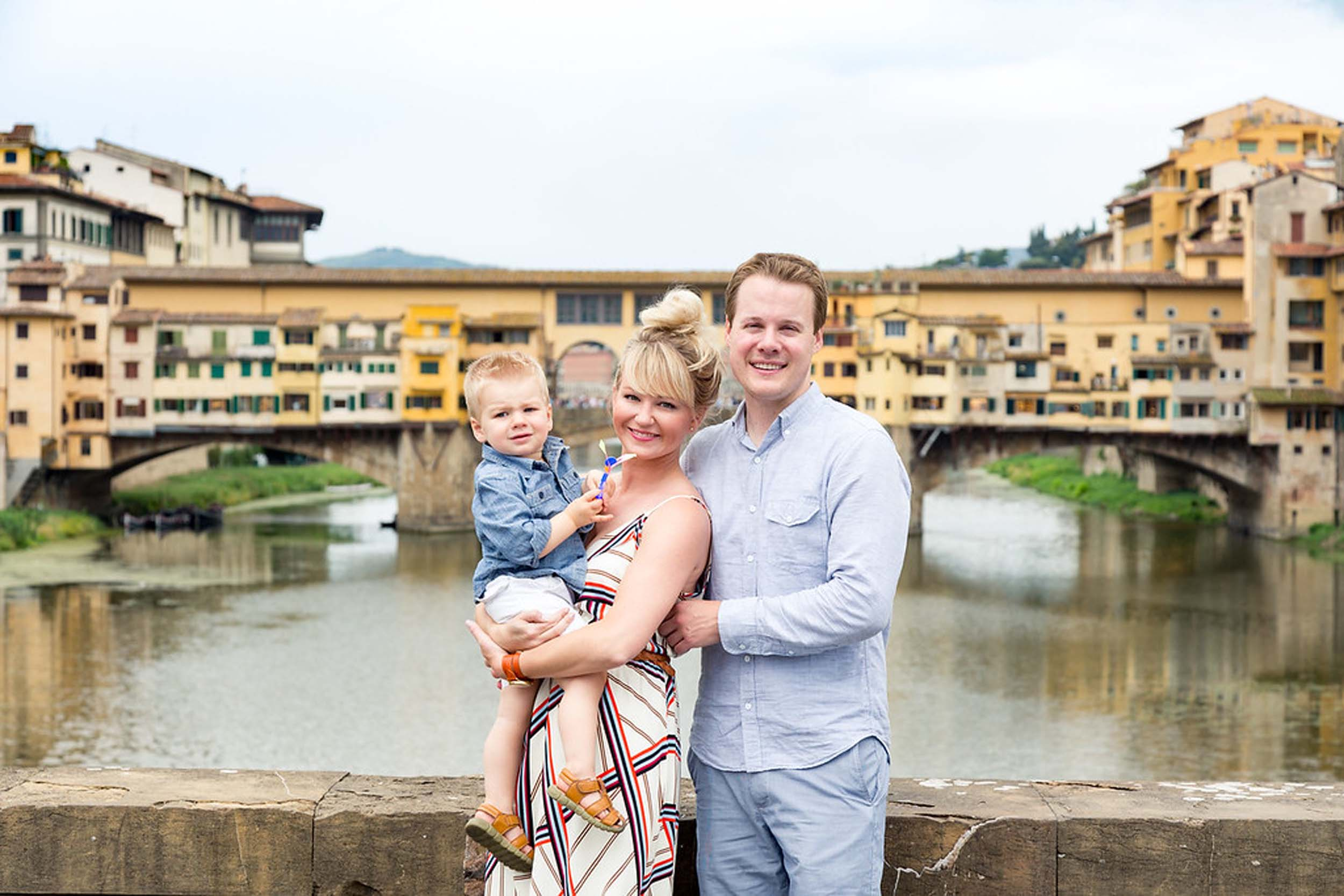 Young family with toddler son in front of Ponte Vecchio on family trip in Florence, Italy