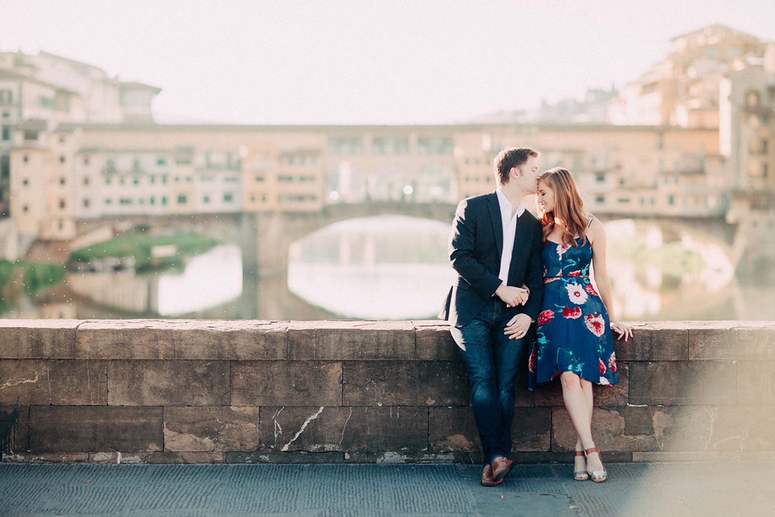 Man kissing his partner's forehead, sitting on bridge ledge in front of Ponte Vecchio on couples trip in Florence, Italy