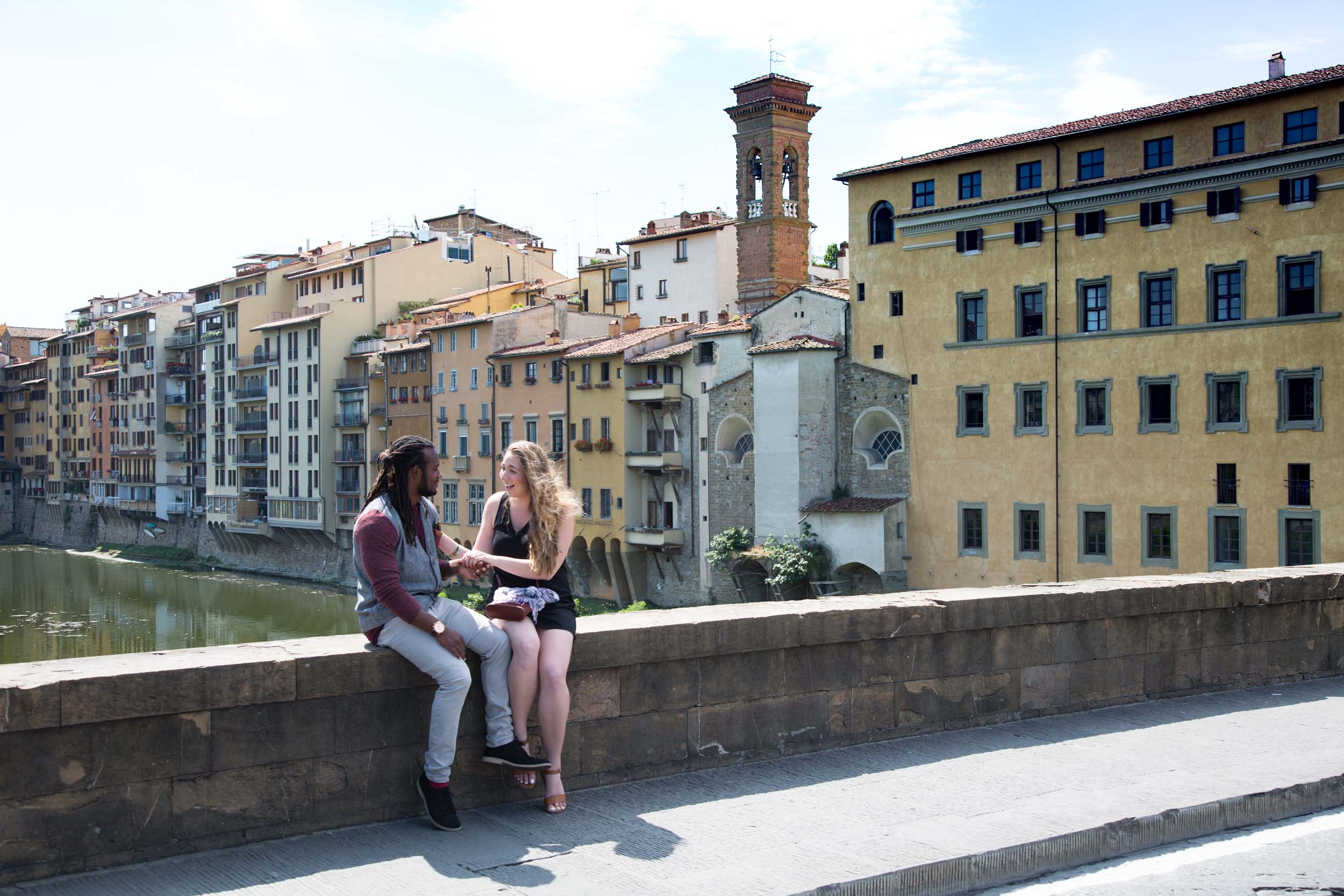 Couple holding hands sitting on bridge ledge in front of Ponte Vecchio on couples trip in Florence, Italy