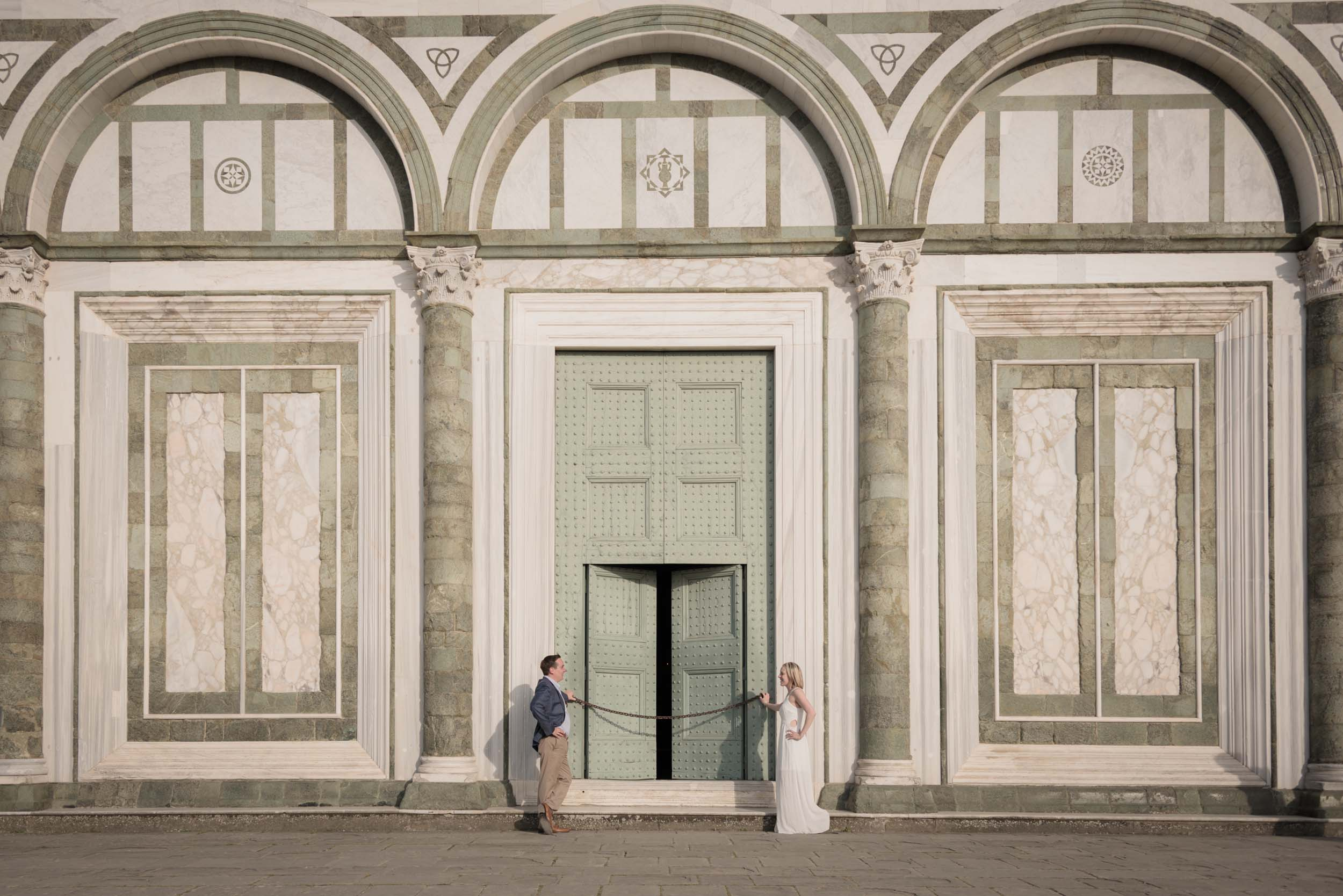 Couple looking at each other in front of The Duomo green door on couples trip in Florence, Italy