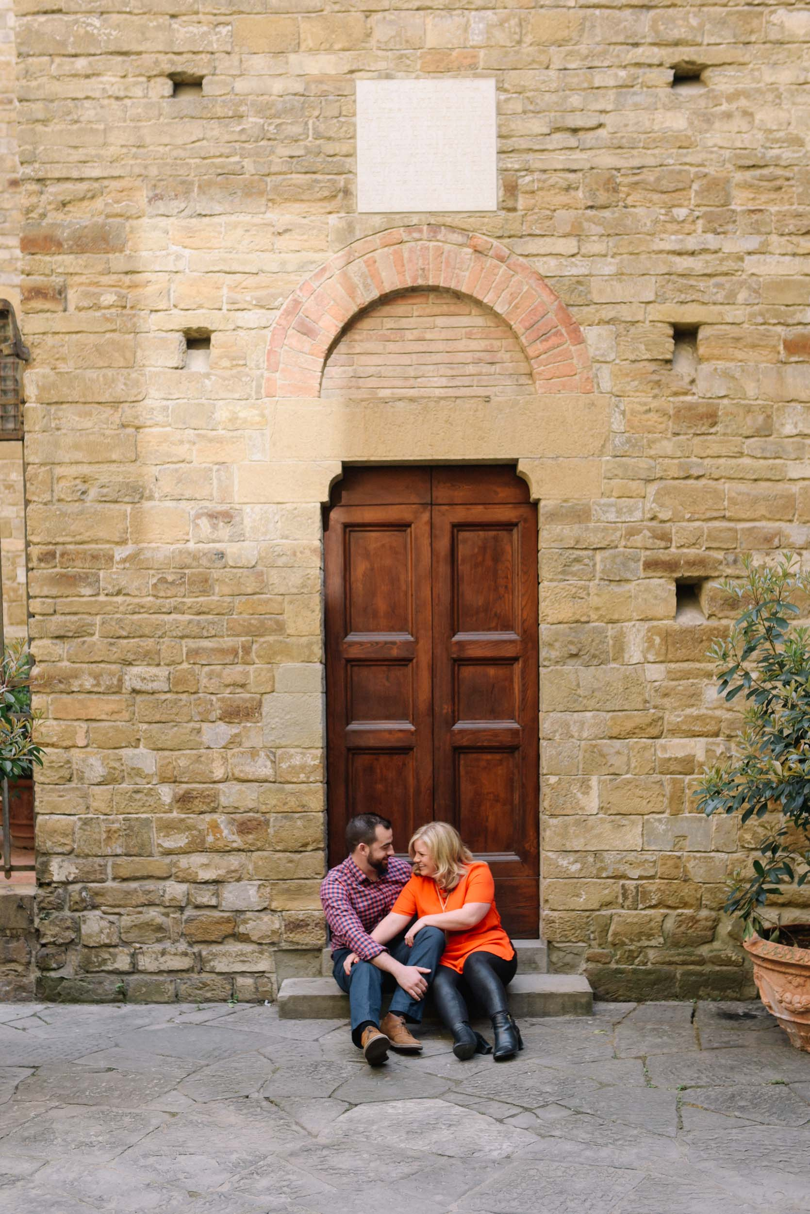 Couple sitting together on steps in small alley in Florence, Italy