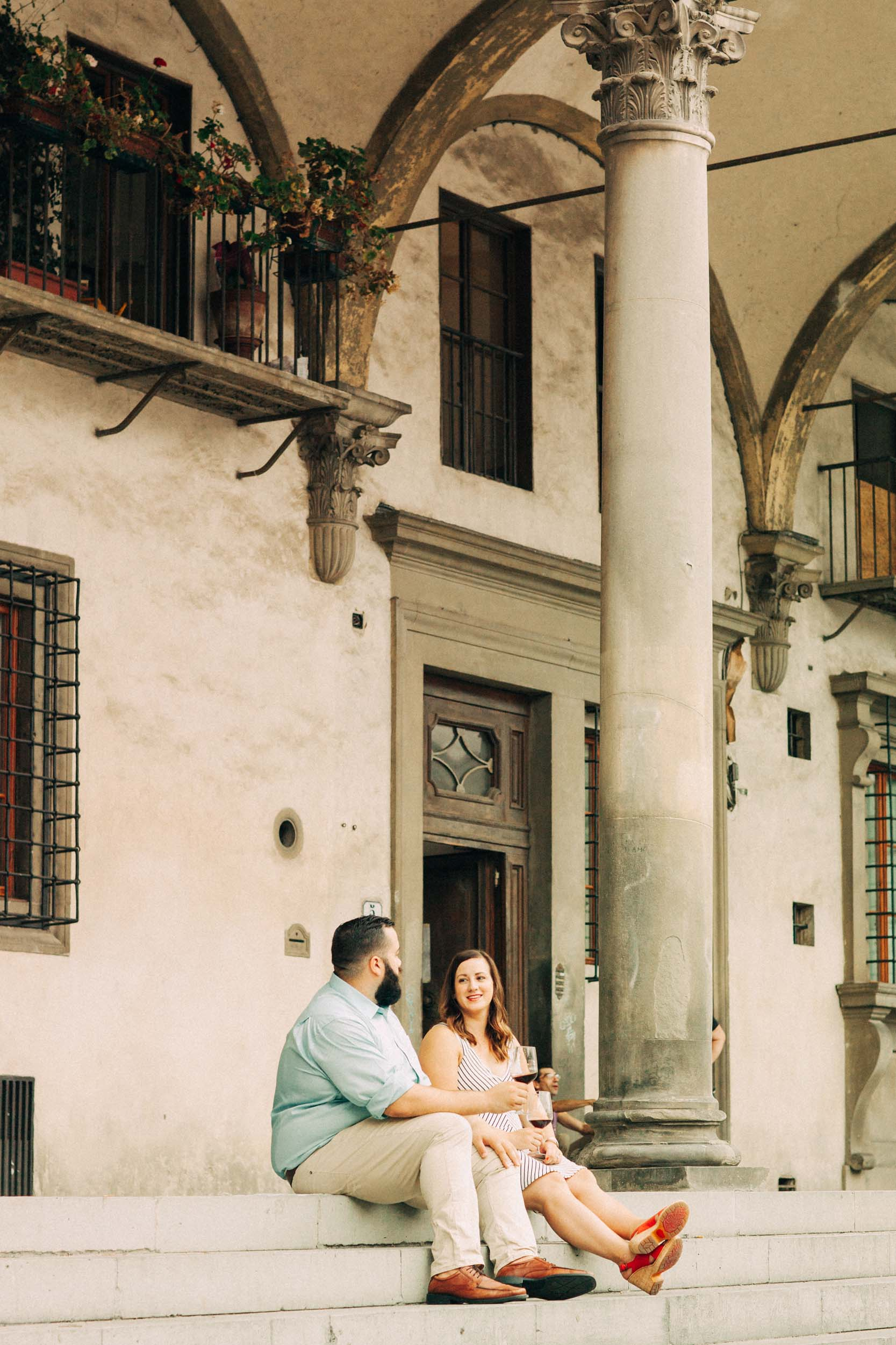 Couple sitting on steps together with red wine in Florence, Italy