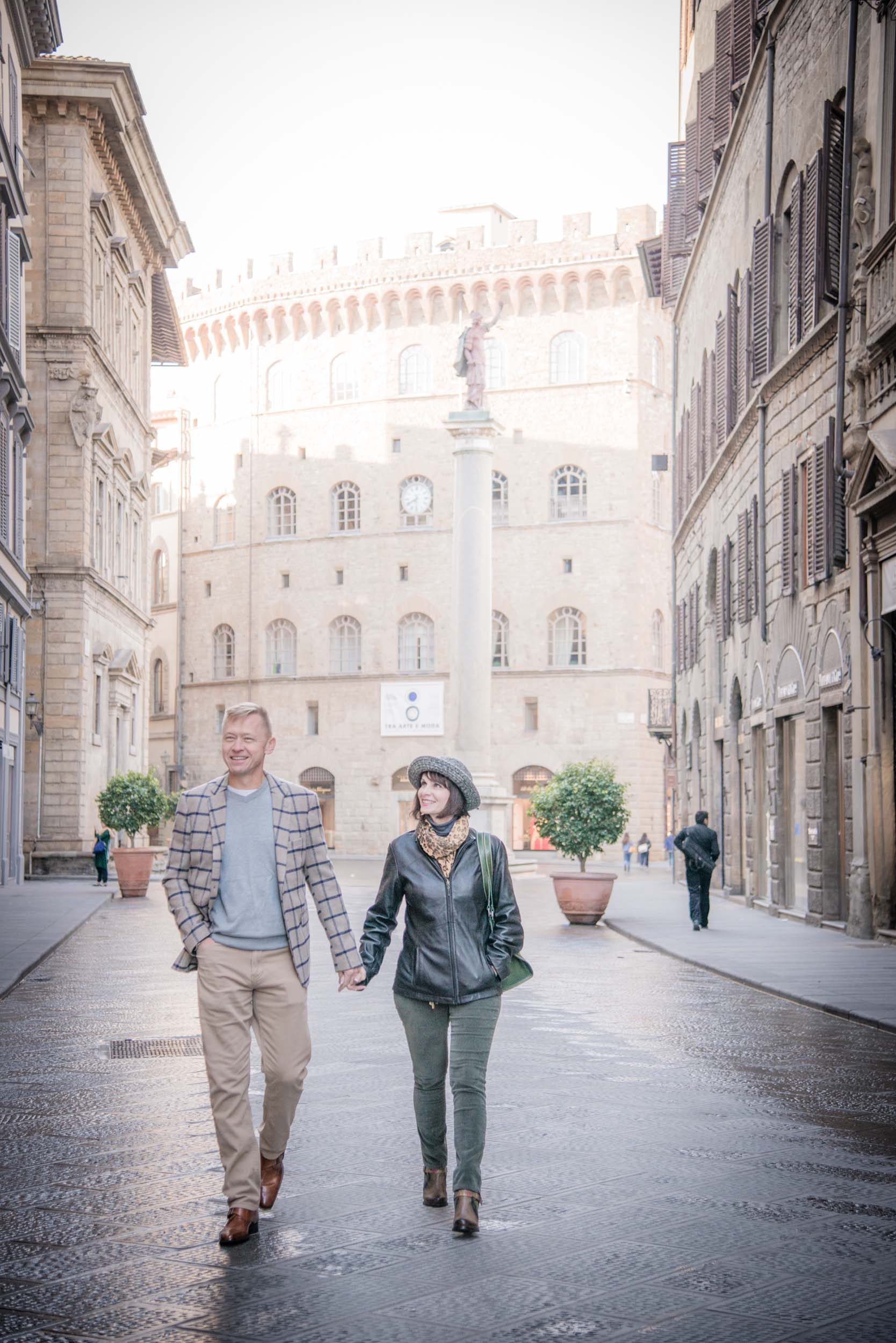 Couple holding hands and walking down a street in Florence, Italy