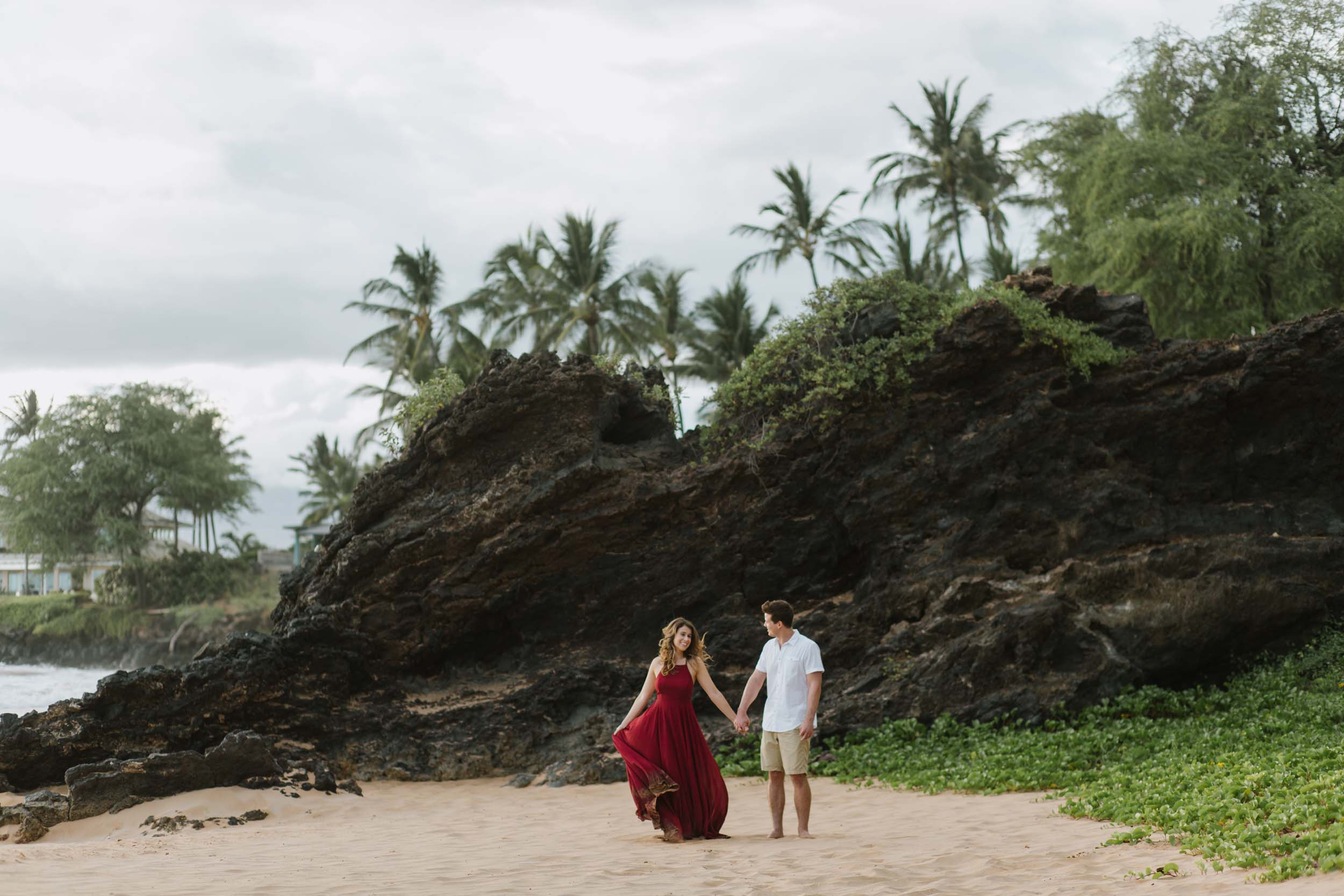 Couple holding hands and walking across a sandy beach in Maui, USA