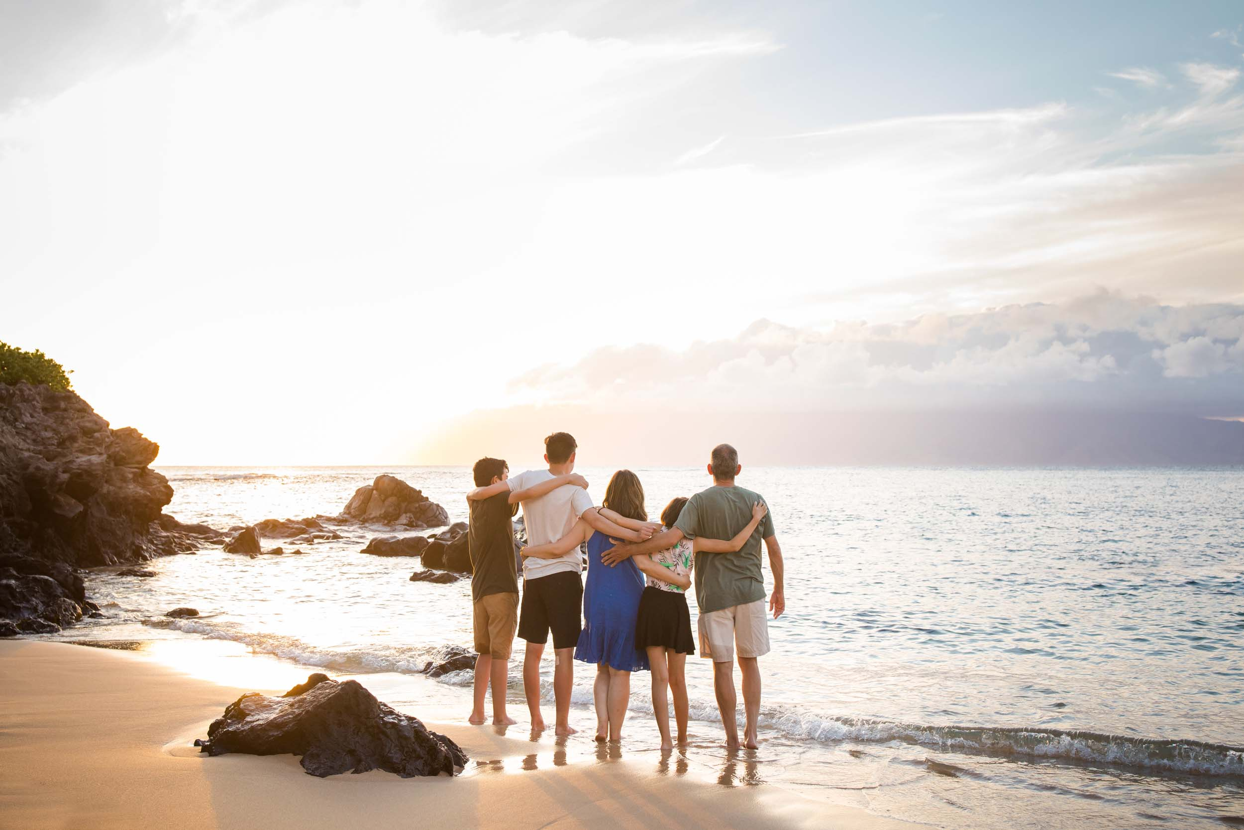 Family staring out at the ocean with their arms around each other in Maui, USA