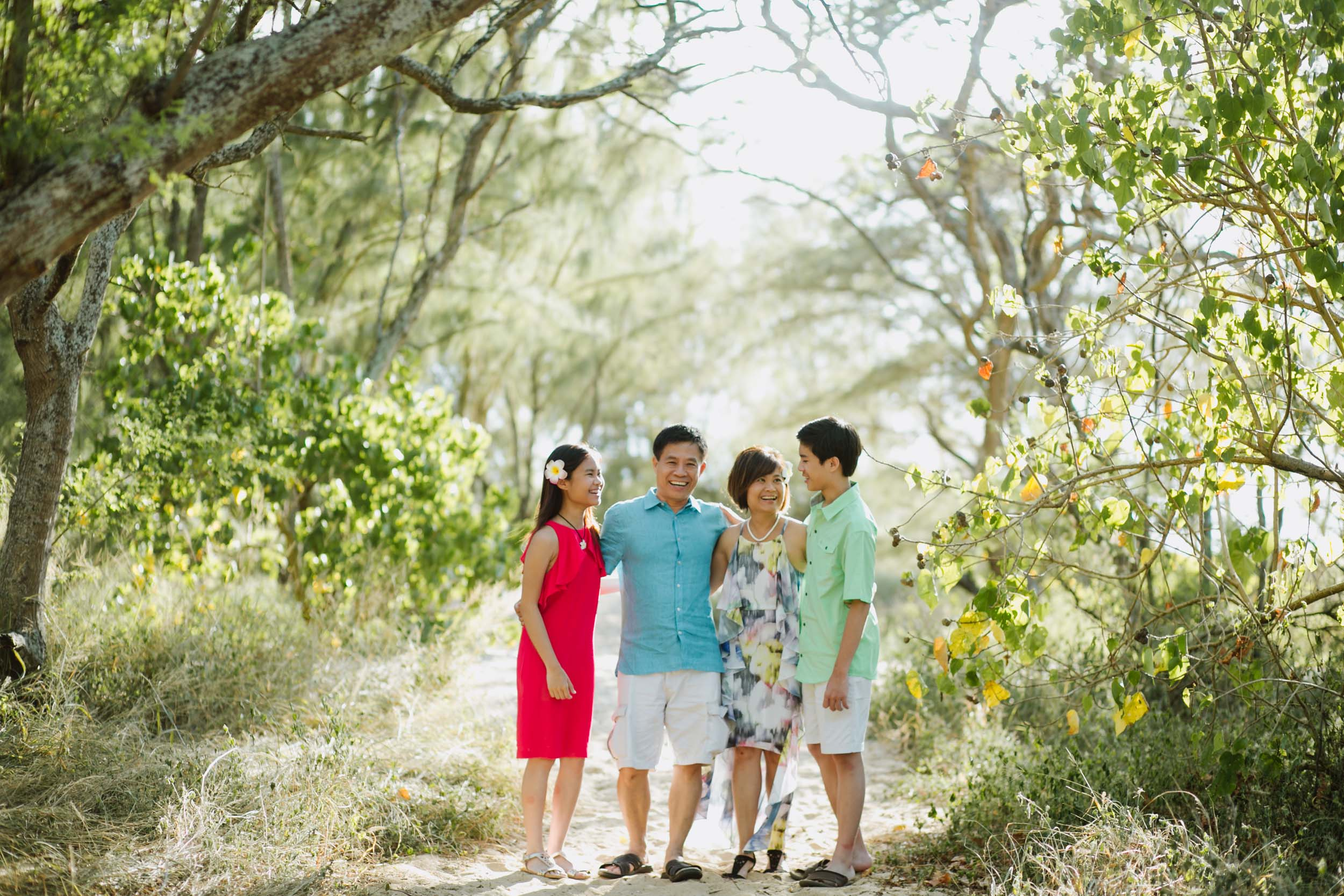 Family standing together along a sandy pathway surrounded by bright green foliage in Maui, USA