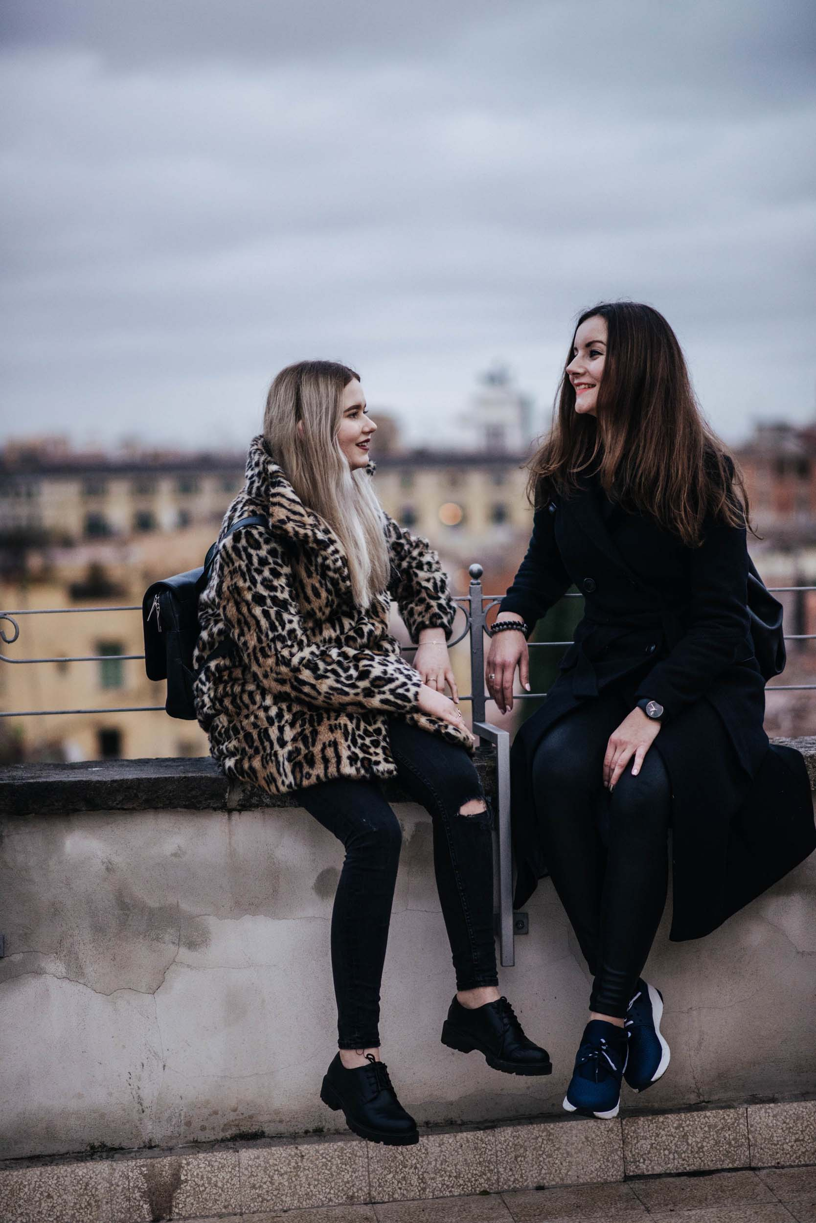 Sisters sitting on wall ledge smiling on a family trip in Rome, Italy