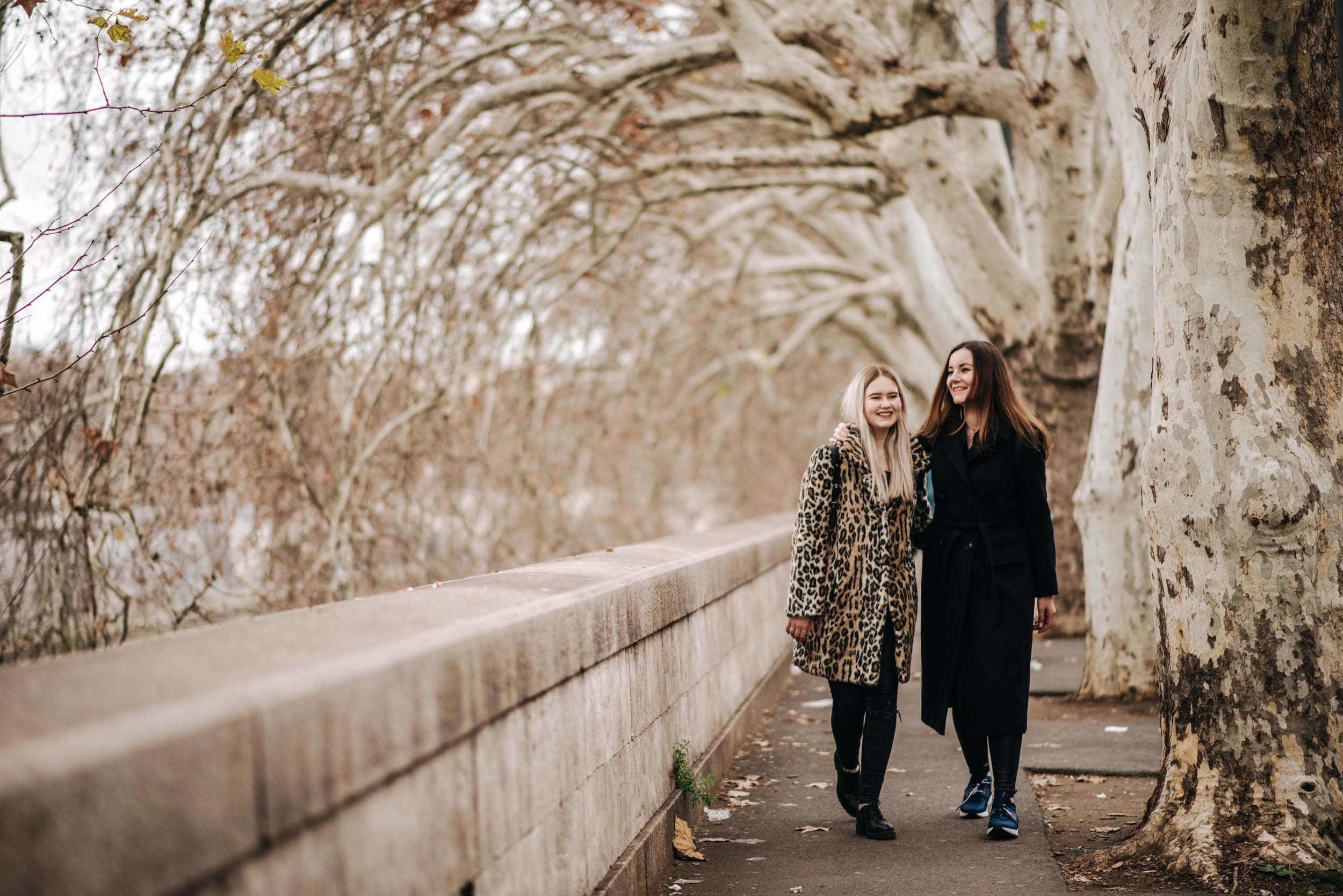 Sisters standing together on walkway in autumn on a family trip in Rome, Italy