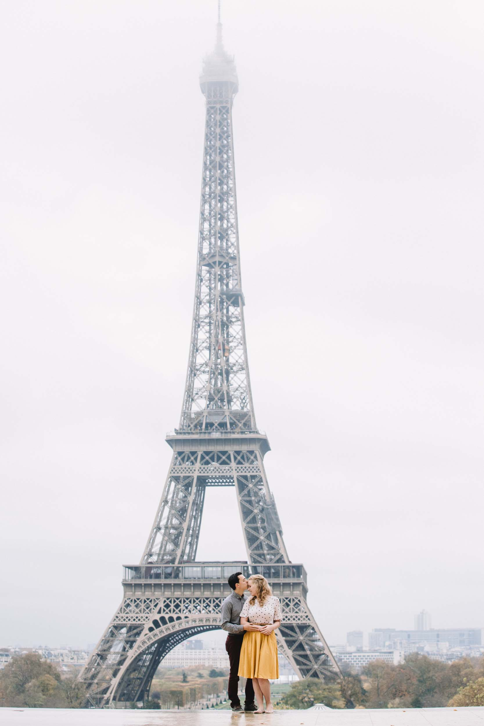 Couple holding each other and kissing with the Eiffel Tower in the background in Paris, France