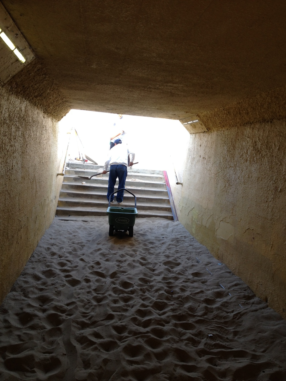 Sand gets carted up steps to beach