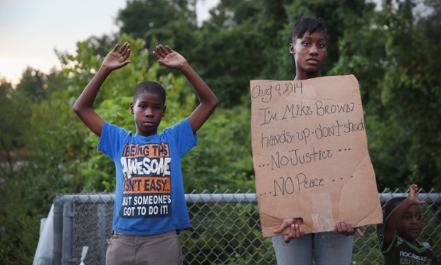 Leo Walker, left, and his sister Letrece, right, protest the killing of Michael Brown on Aug. 17, 2014 in Ferguson, Mo.